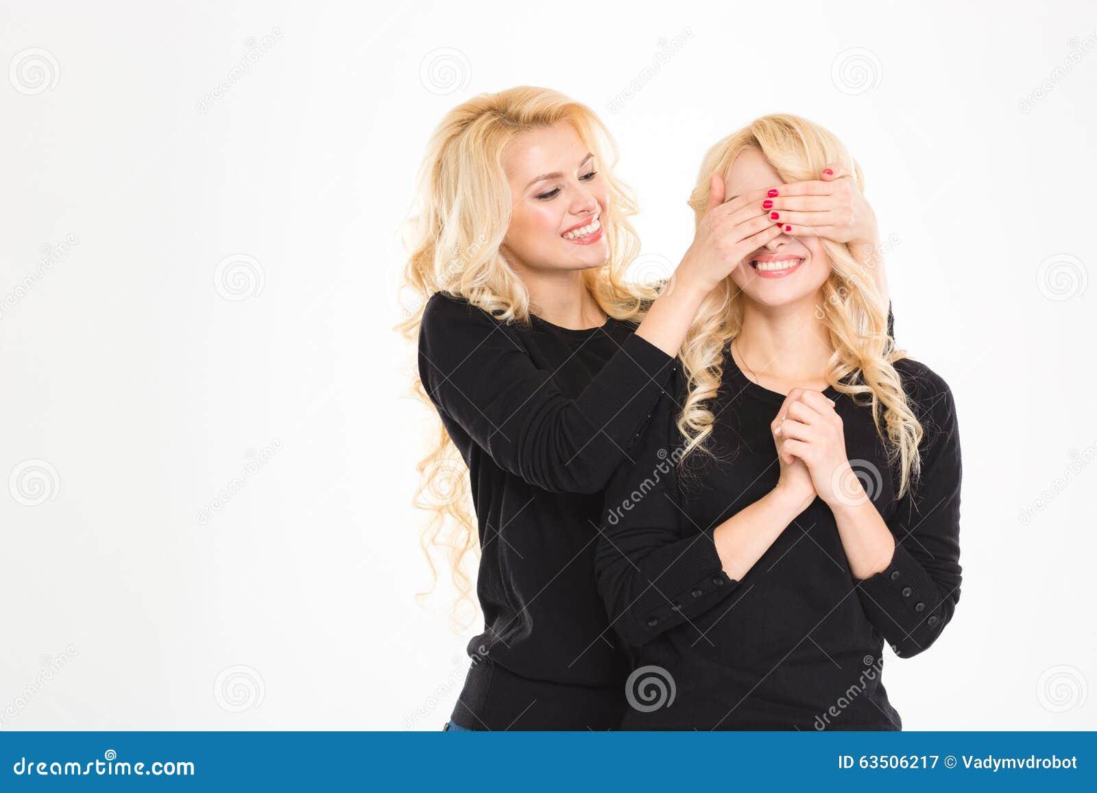 Recht froher blonder Schwesterzwilling bedeckte die Augen zu anderen lokalisiert