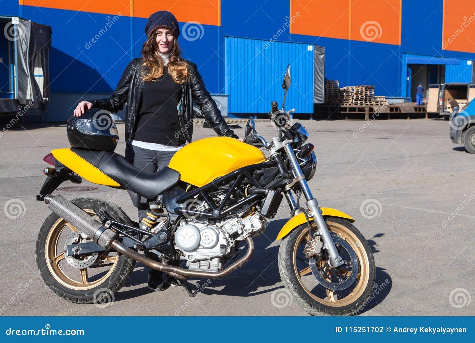 Recht glückliche Frau mit ihrem gelieferten Motorrad steht nahe bei dem Frachtfirmenlager und empfängt Fahrrad