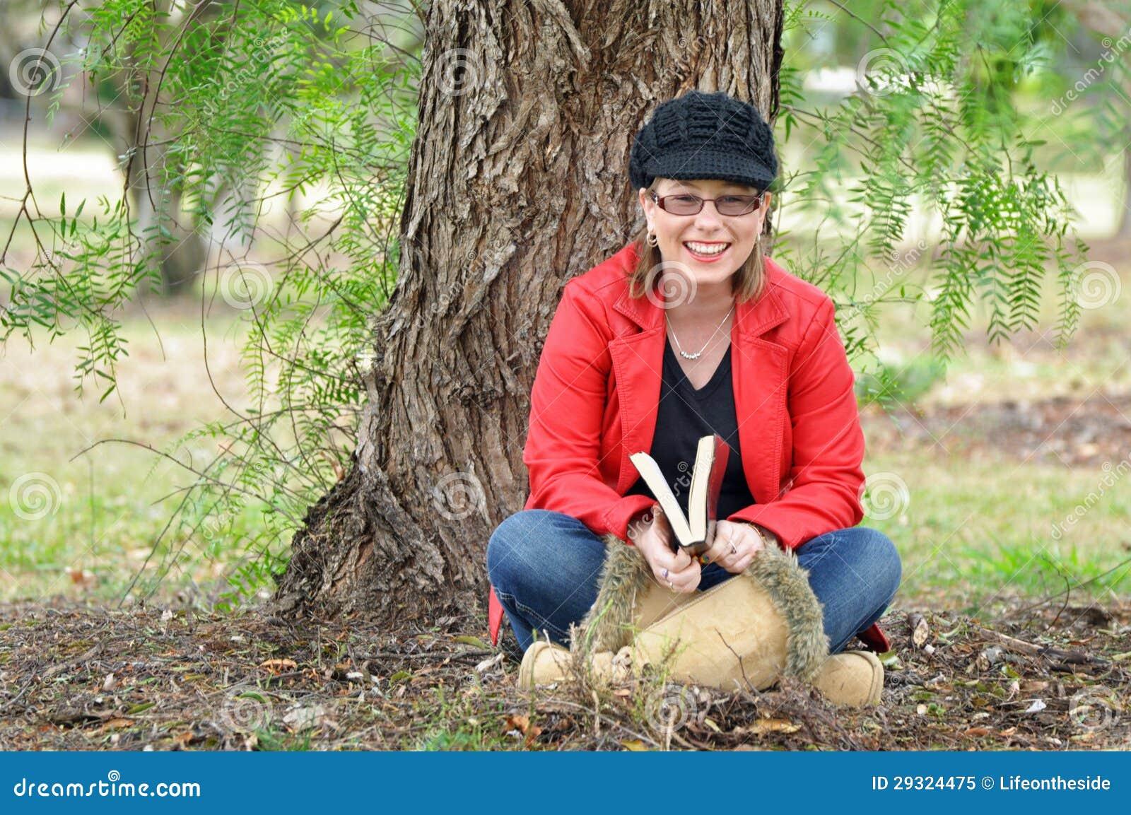 Recht glückliche junge Frau, die draußen unter Baum lacht