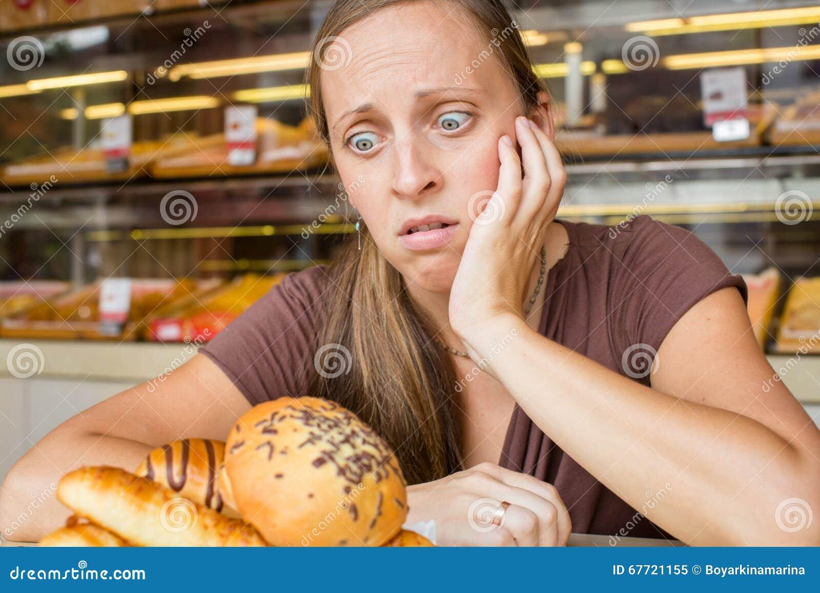 Recht junge Frau, die Bonbons im Café isst Schlechte Gewohnheiten gesundheit