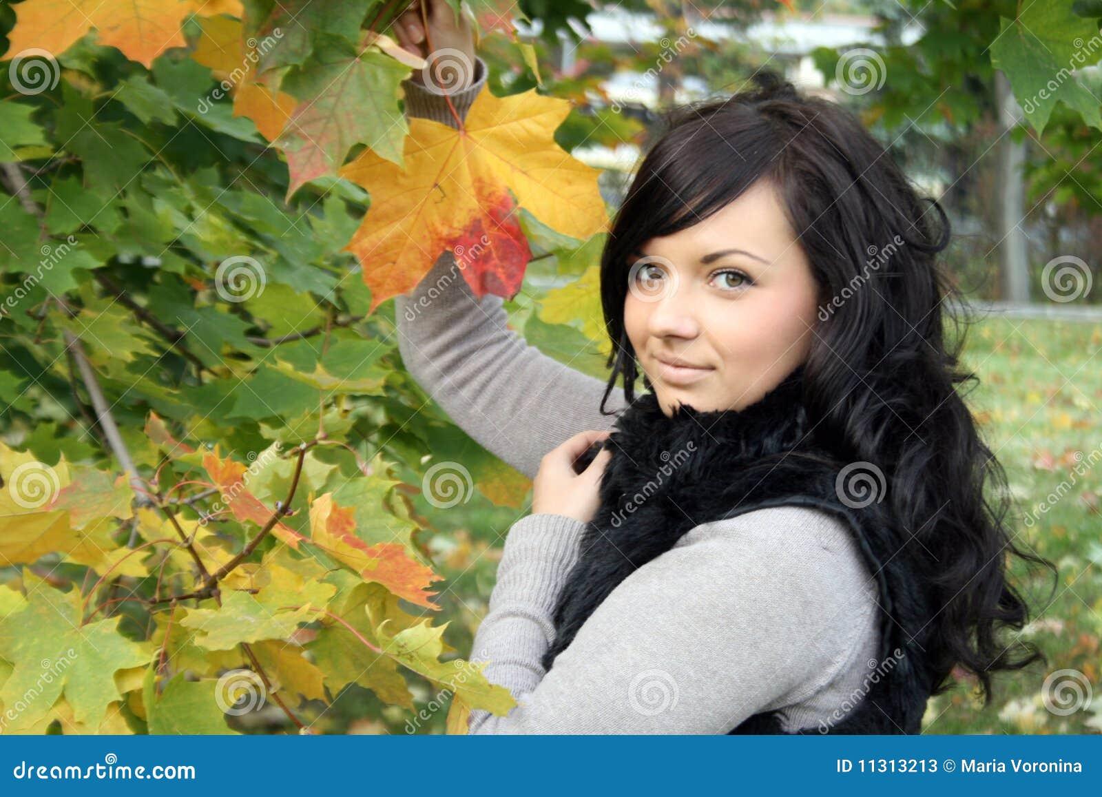 Recht junge Frau, die nahes Ahornholz steht
