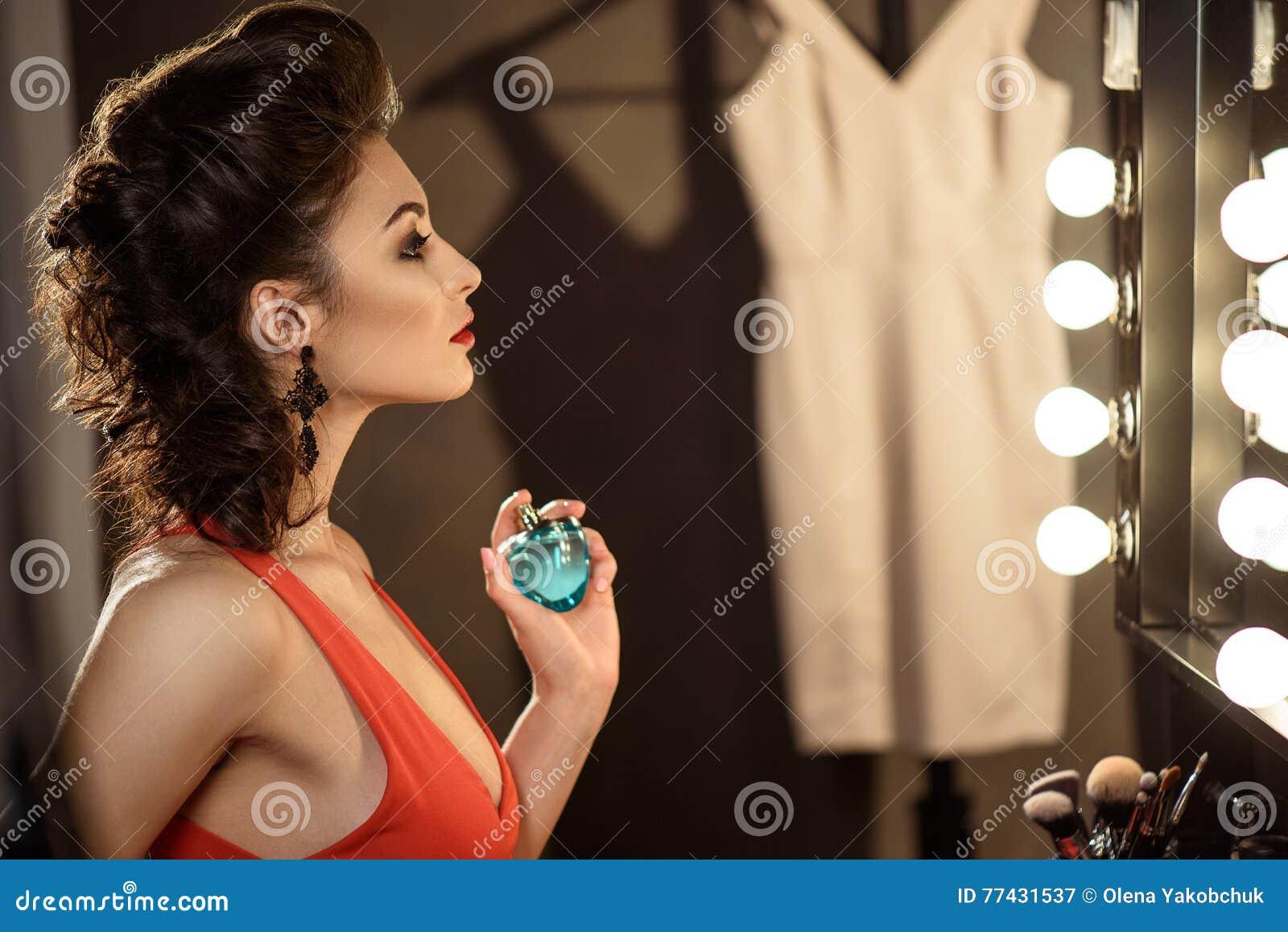 Recht junge Frau, die sich parfümiert