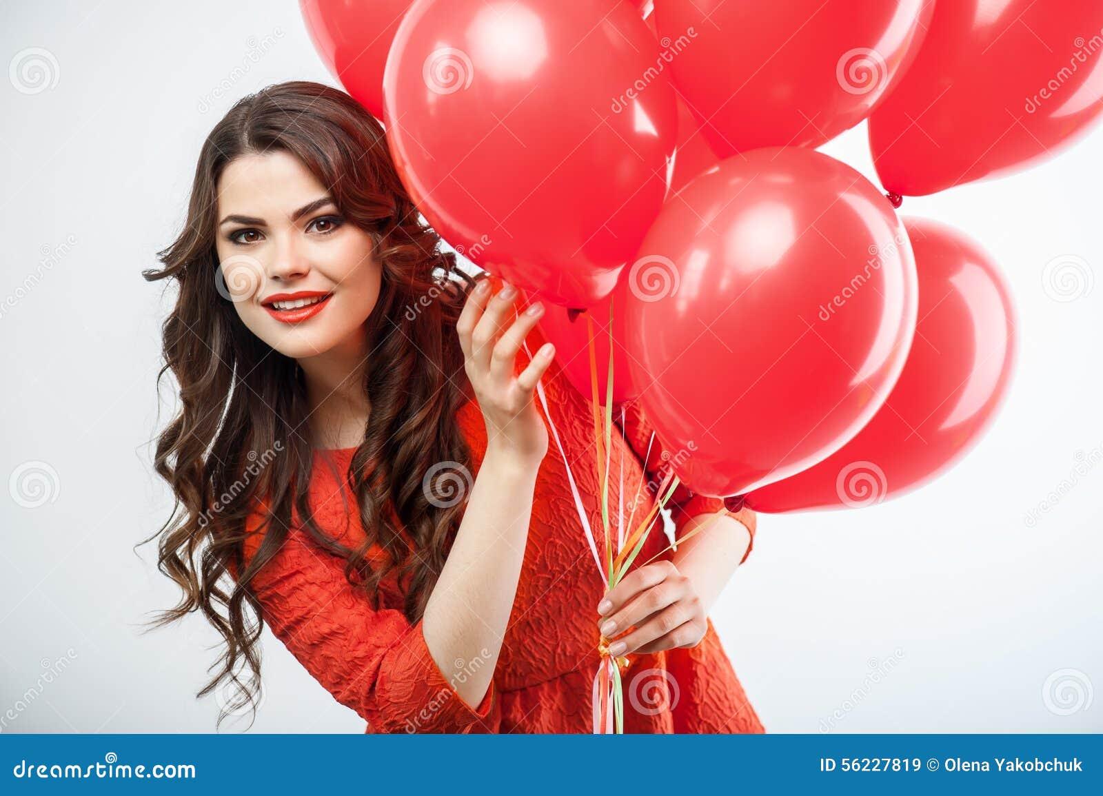 Recht junge Frau im roten Kleid feiert