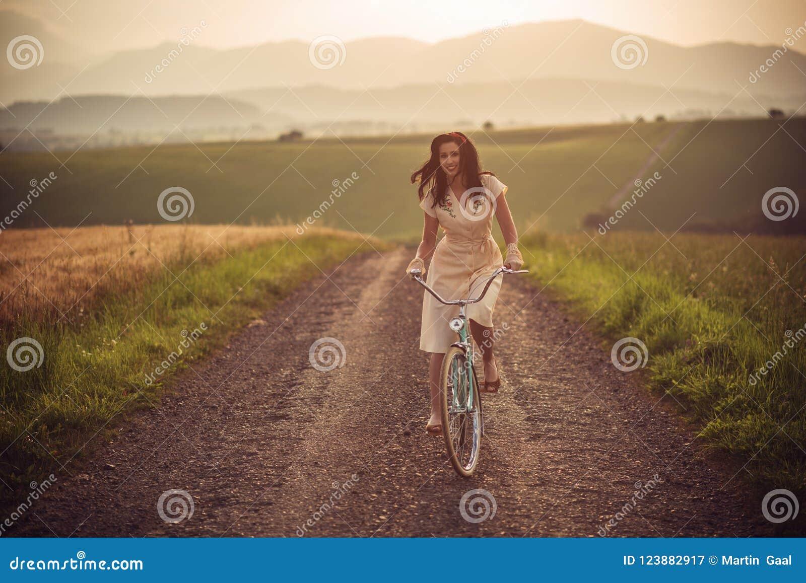 Recht junge smilling Frau mit Retro- Fahrrad im Sonnenuntergang auf der Straße, alte Zeiten der Weinlese, Mädchen im Retrostil au