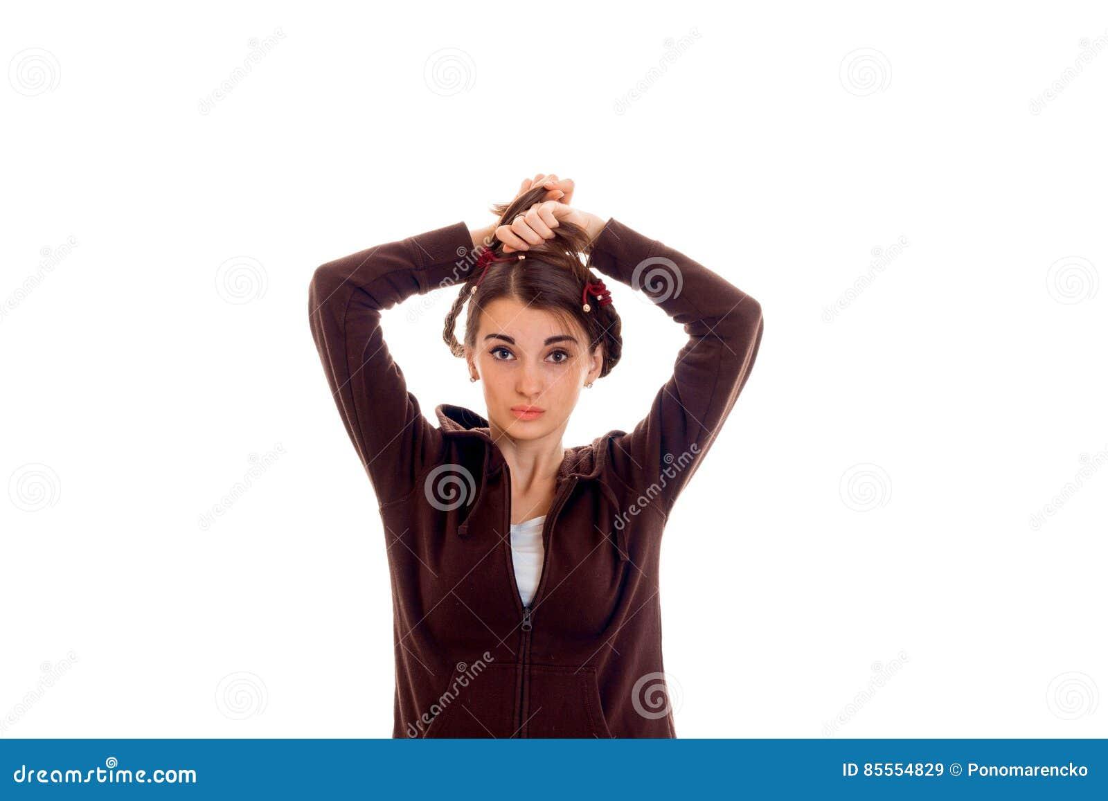 Recht junges Mädchen in der braunen Sportkleidung, welche die Kamera und die Aufstellung lokalisiert auf weißem Hintergrund betra