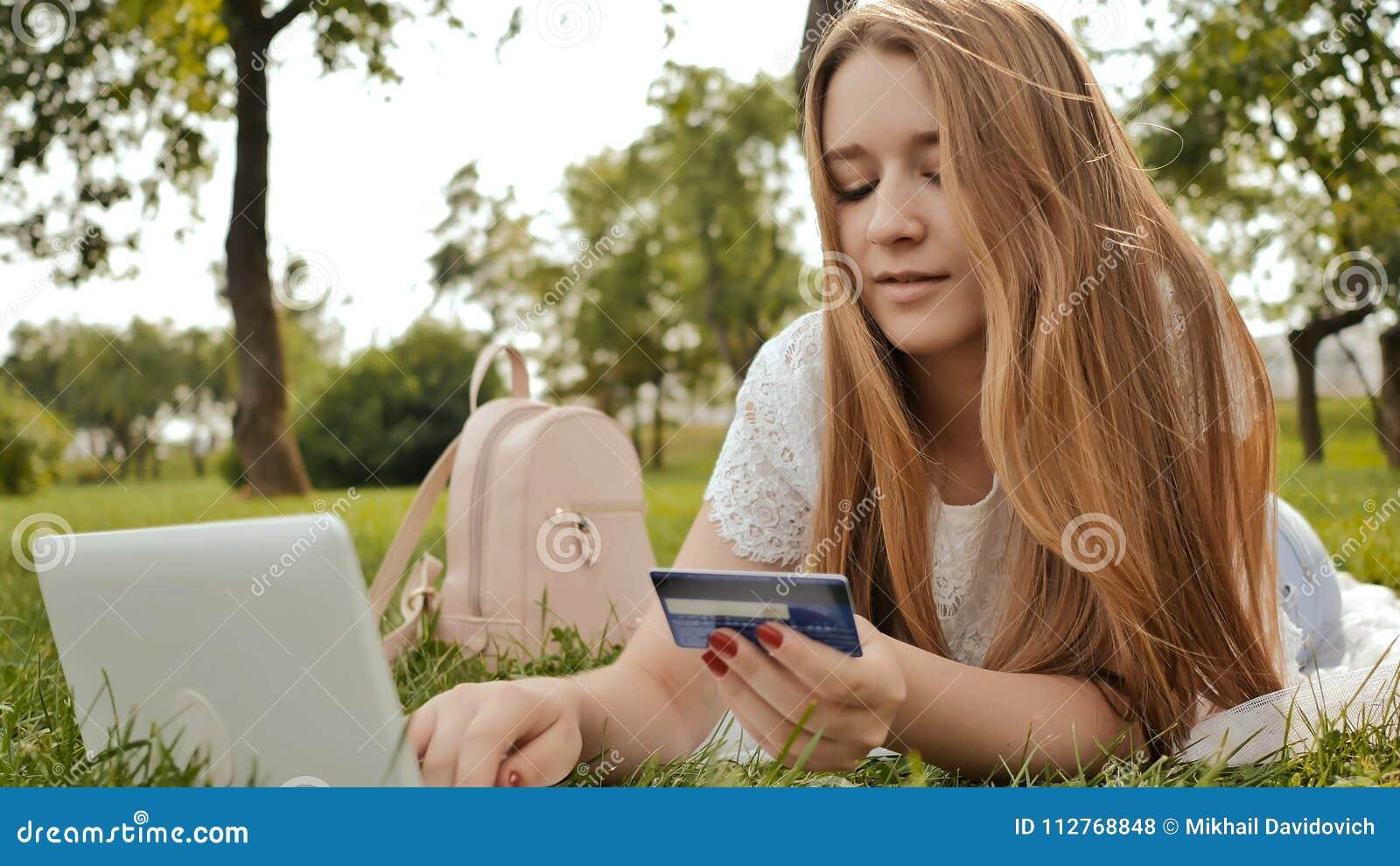 Recht junges Studentenmädchen schließt Käufe on-line unter Verwendung einer Kreditkarte und einer Laptop-Computers ab