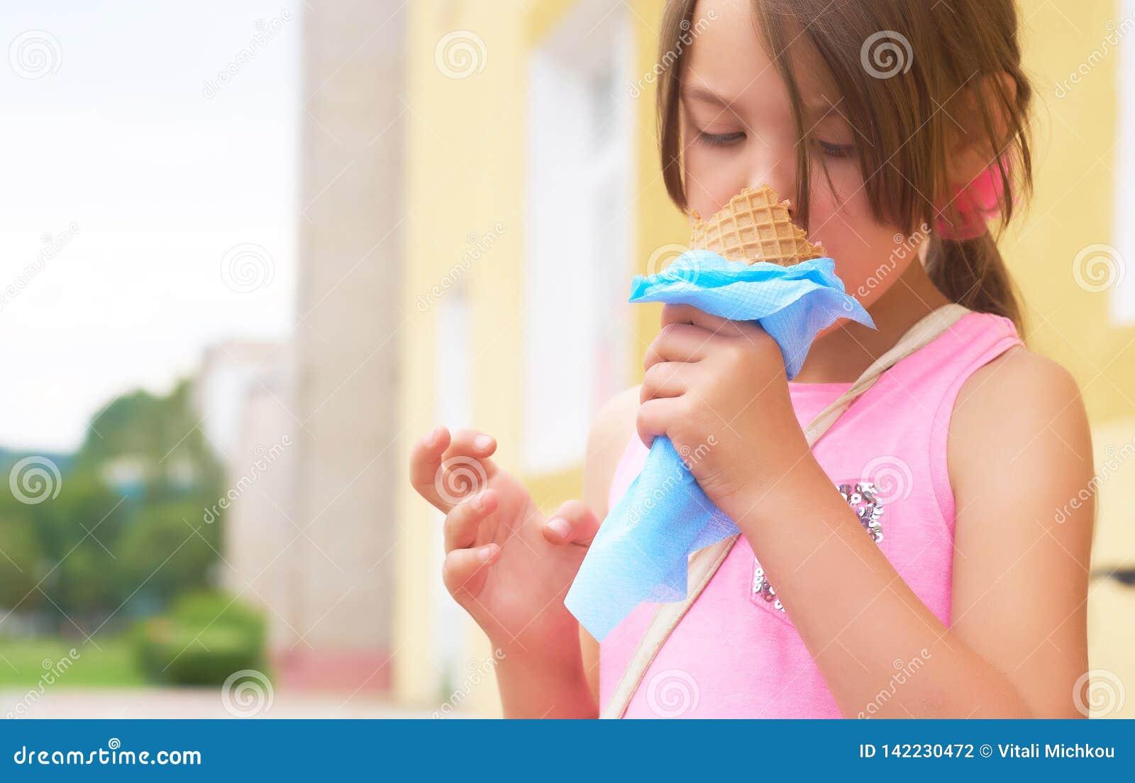 Recht kleines Mädchen, das große Eiscreme im glücklichen Lachen des Waffelkegels auf Naturhintergrund leckend isst