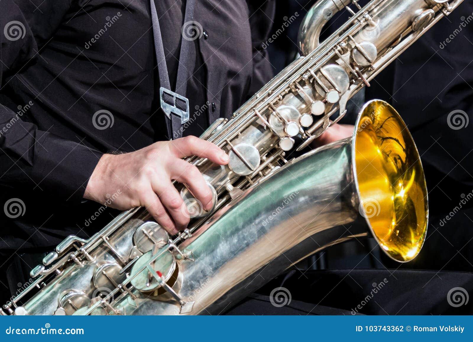 Rechts van de musicus in een zwart overhemd rust op een saxofoon-bariton Close-up