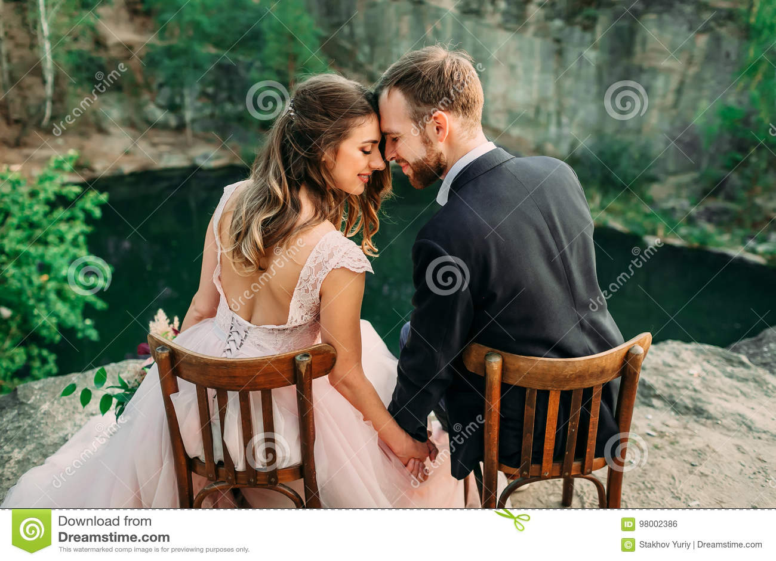 Recienes casados que se sientan en el borde del barranco y de los pares que se miran con dulzura y amor Novia y novio
