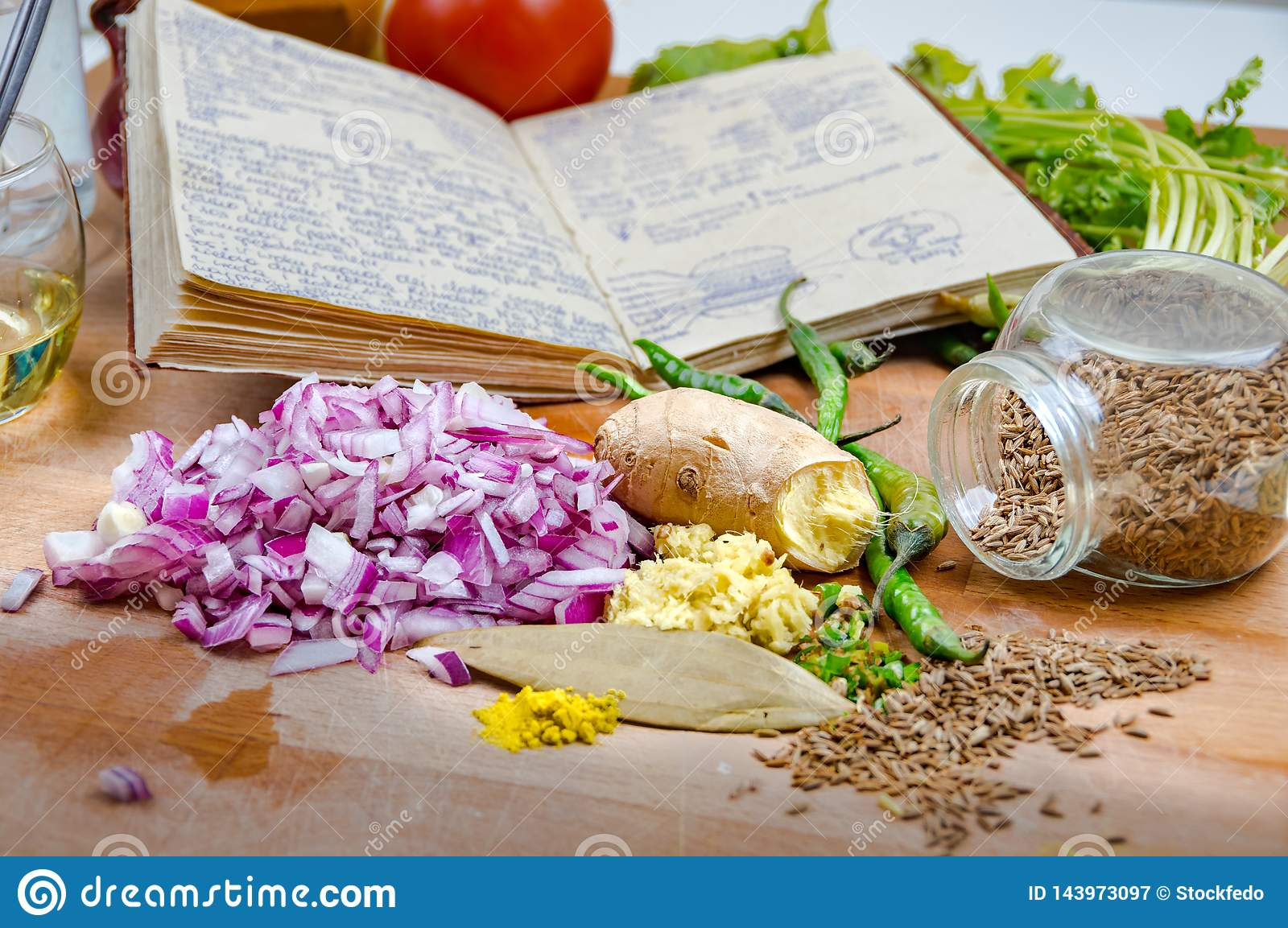 Notes with recipes surrounded by spices and vegetables on a wooden table in the kitchen