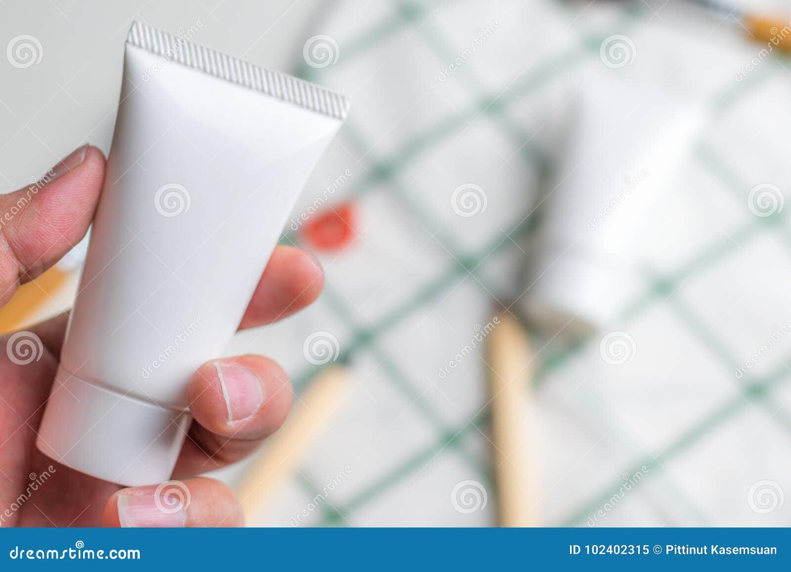 Recipientes cosméticos da garrafa com as folhas ervais verdes, etiqueta vazia