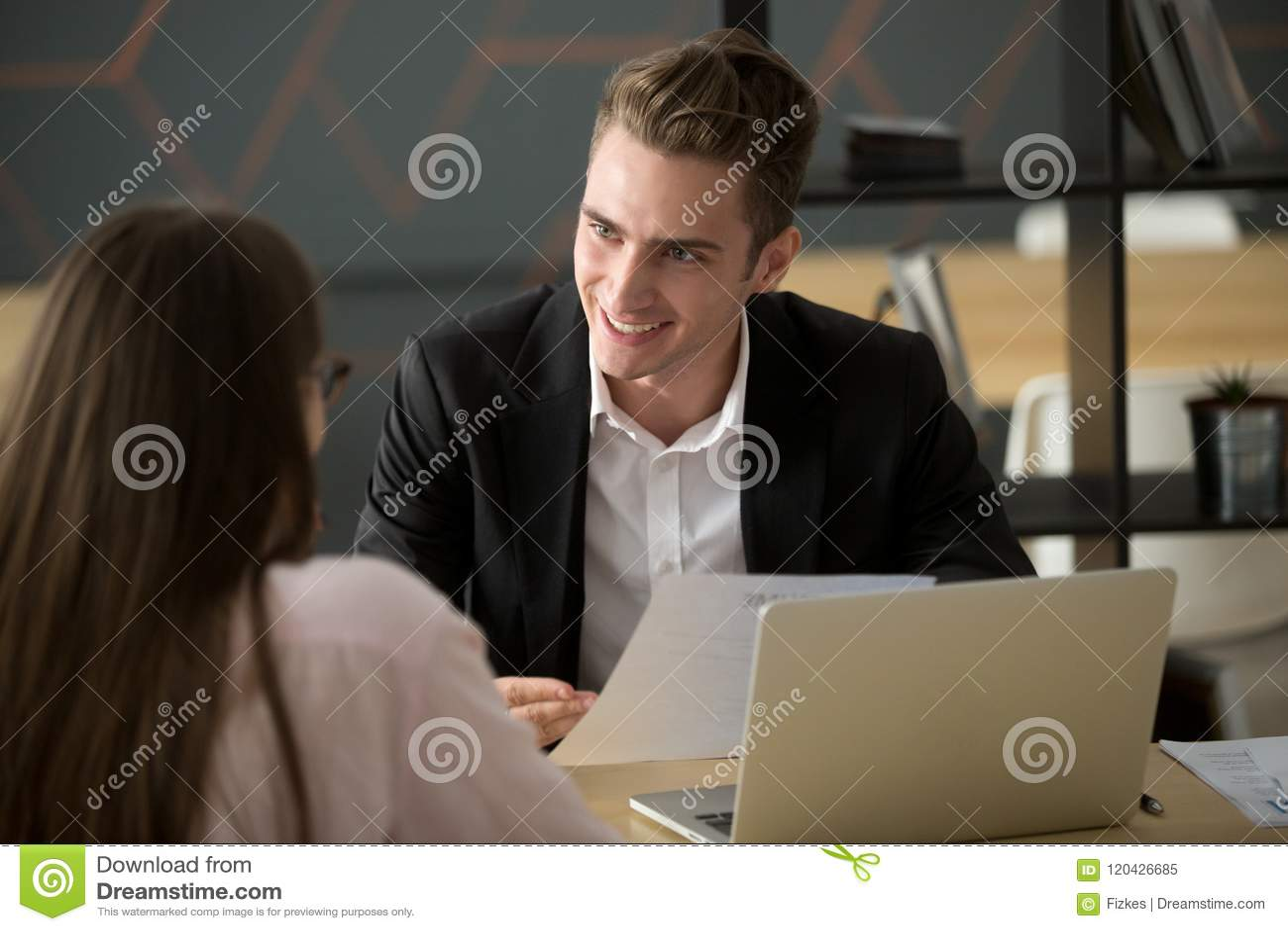 Reclutador masculino sonriente que discute el cv con el candidato de trabajo femenino