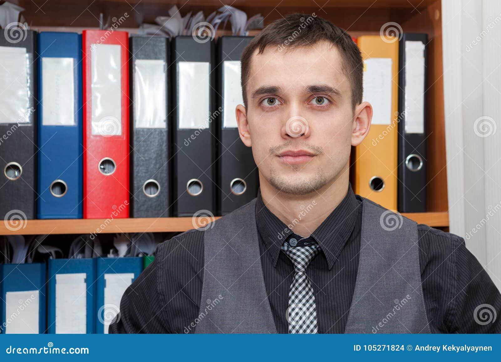 Recordkeeper financier caucasien se tenant devant le coffret avec des dossiers de documentation de couleur