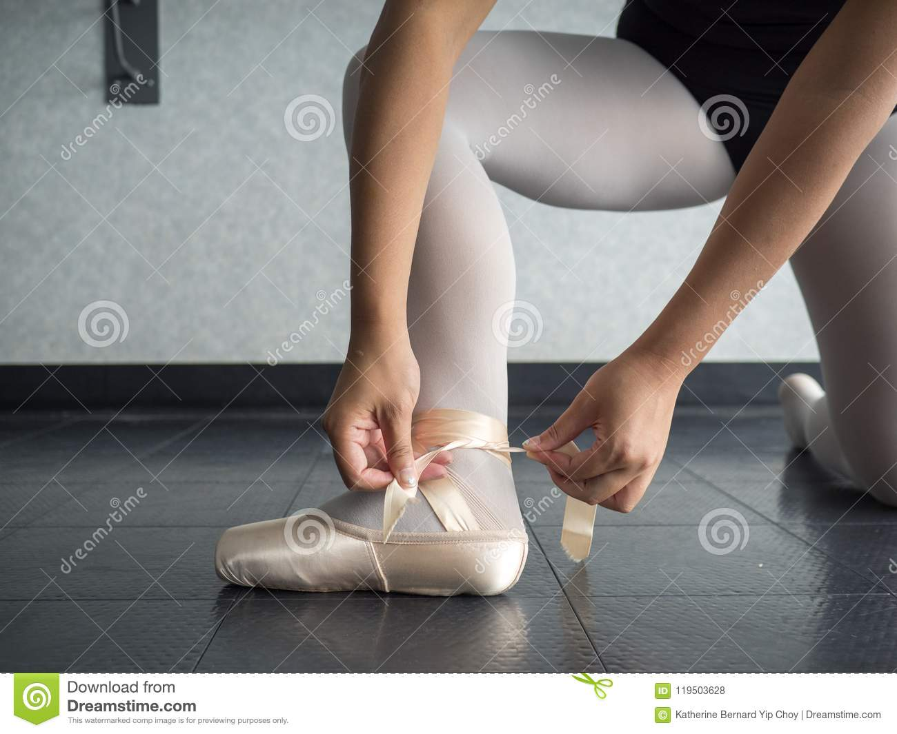 Recreational young female ballet dancer ballerina, in the studio putting on her pointe shoes, tying up