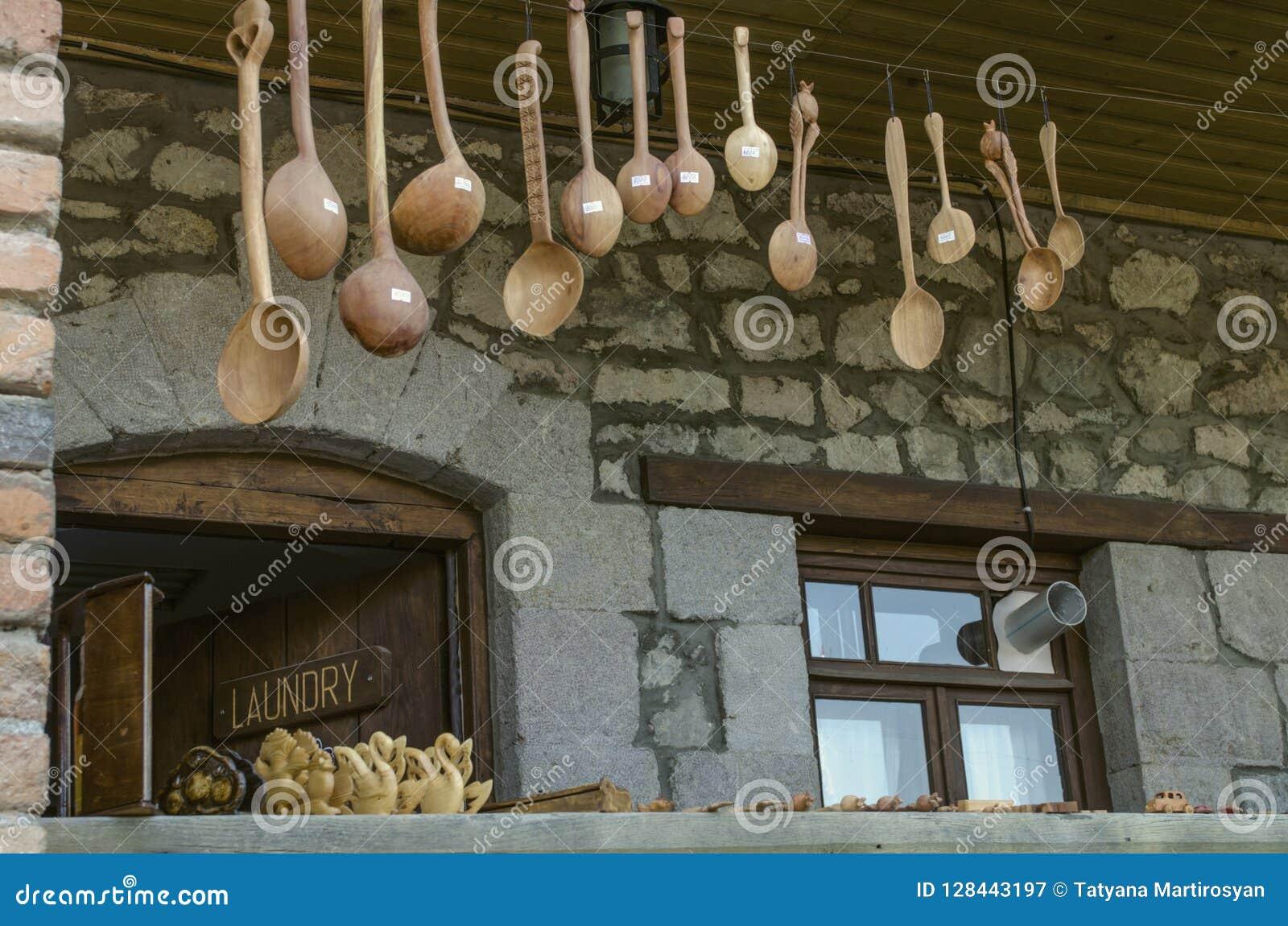 Recuerdos, cucharas y juguetes de madera tallados en el mirador con las columnas del ladrillo en la calle de Sharambeyan en el mu