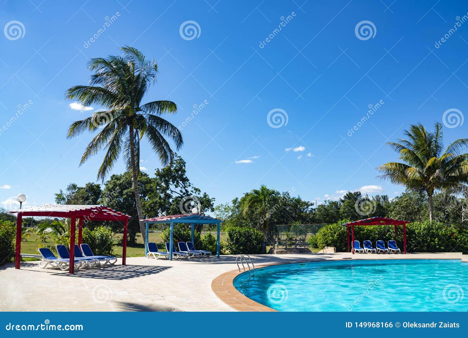 Recurso tropical bonito com piscina, sol-vadios e palmeiras durante um dia ensolarado morno, férias em Cuba