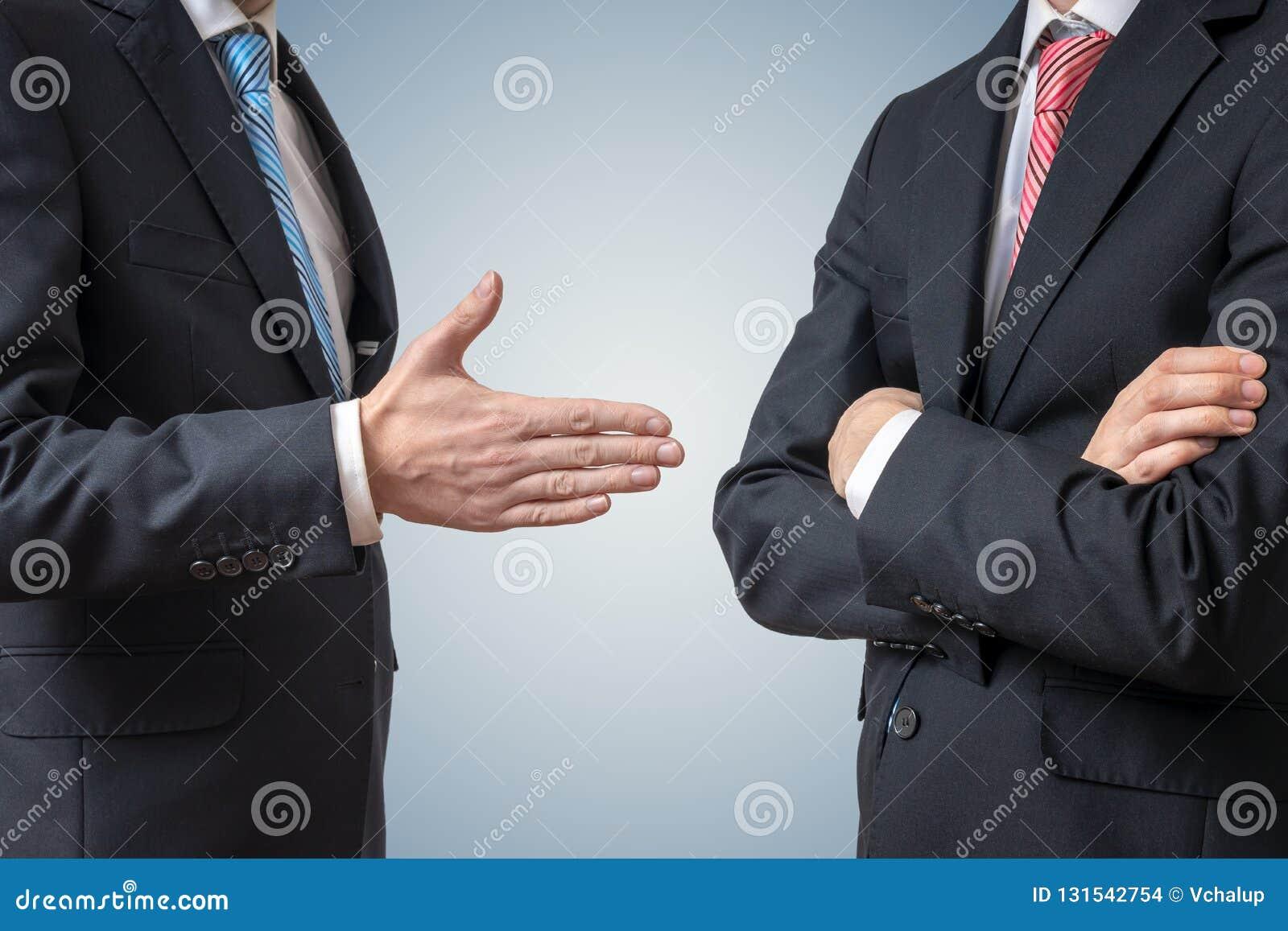Recusa do aperto de mão O homem está recusando a mão da agitação com homem de negócios que está oferecendo sua mão