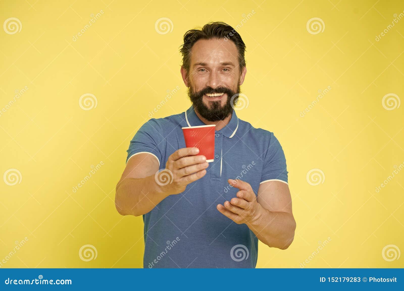 Recyclable кофейная чашка Кофейная чашка бумаги владением человека хипстера зрелая стоит желтая предпосылка t Выпейте его