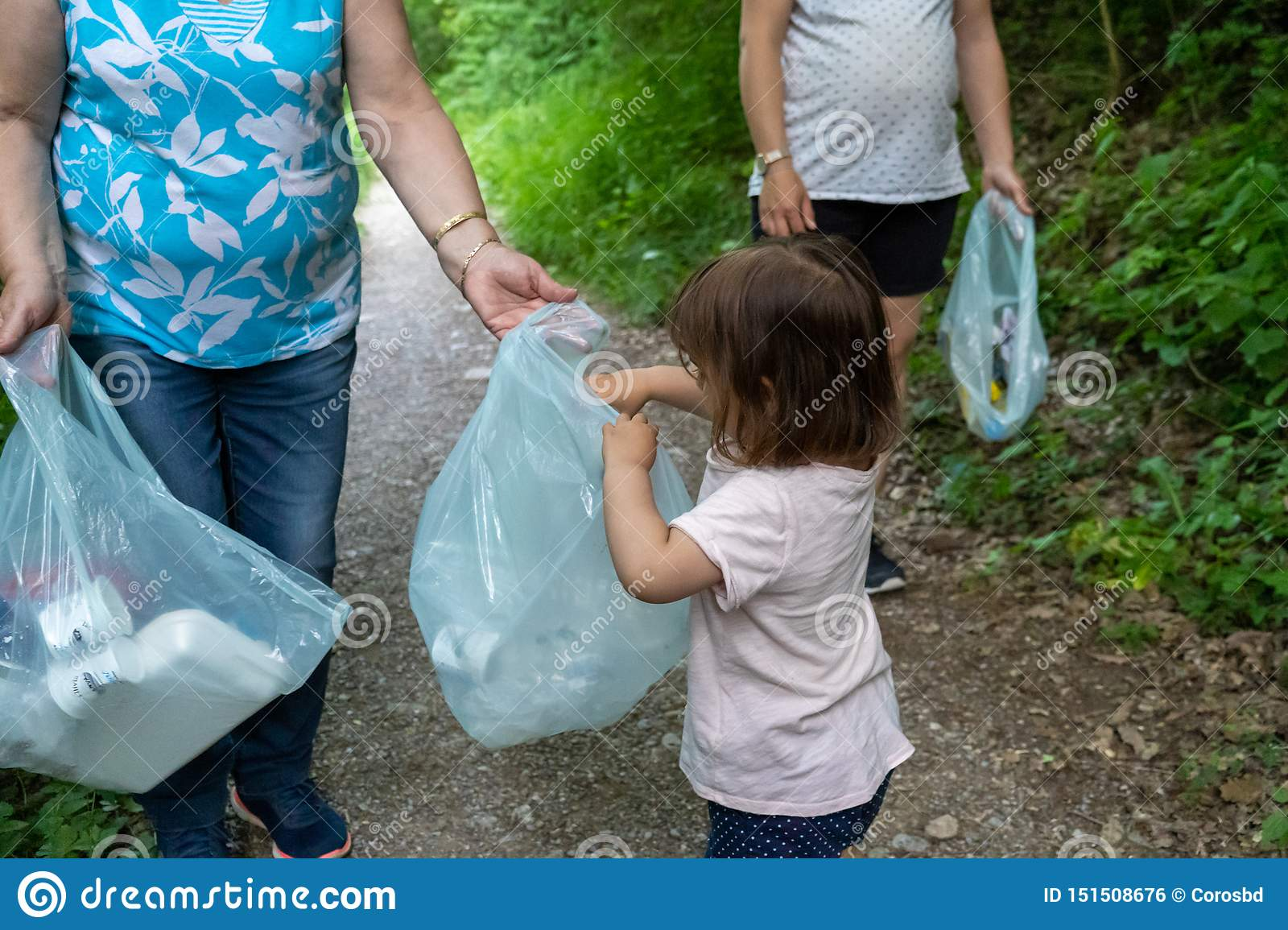 Little girl, pregnant mother and grandmother cleaning the forest of plastics