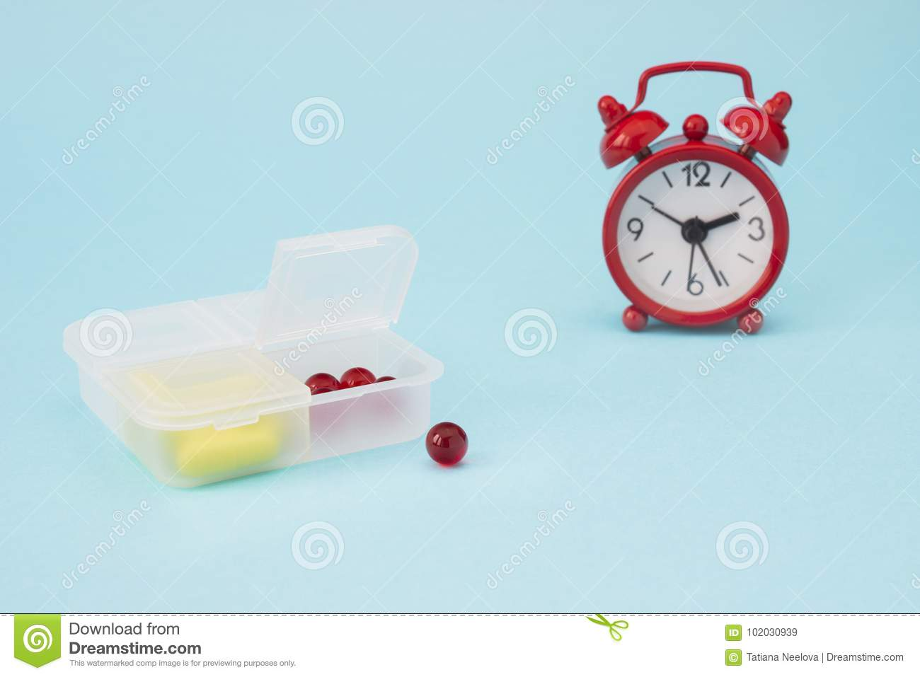 Red alarm clock, pharmaceutical pills, tablets and yellow capsules spilling out of daily pill box. Medical concept photo, pharmacy