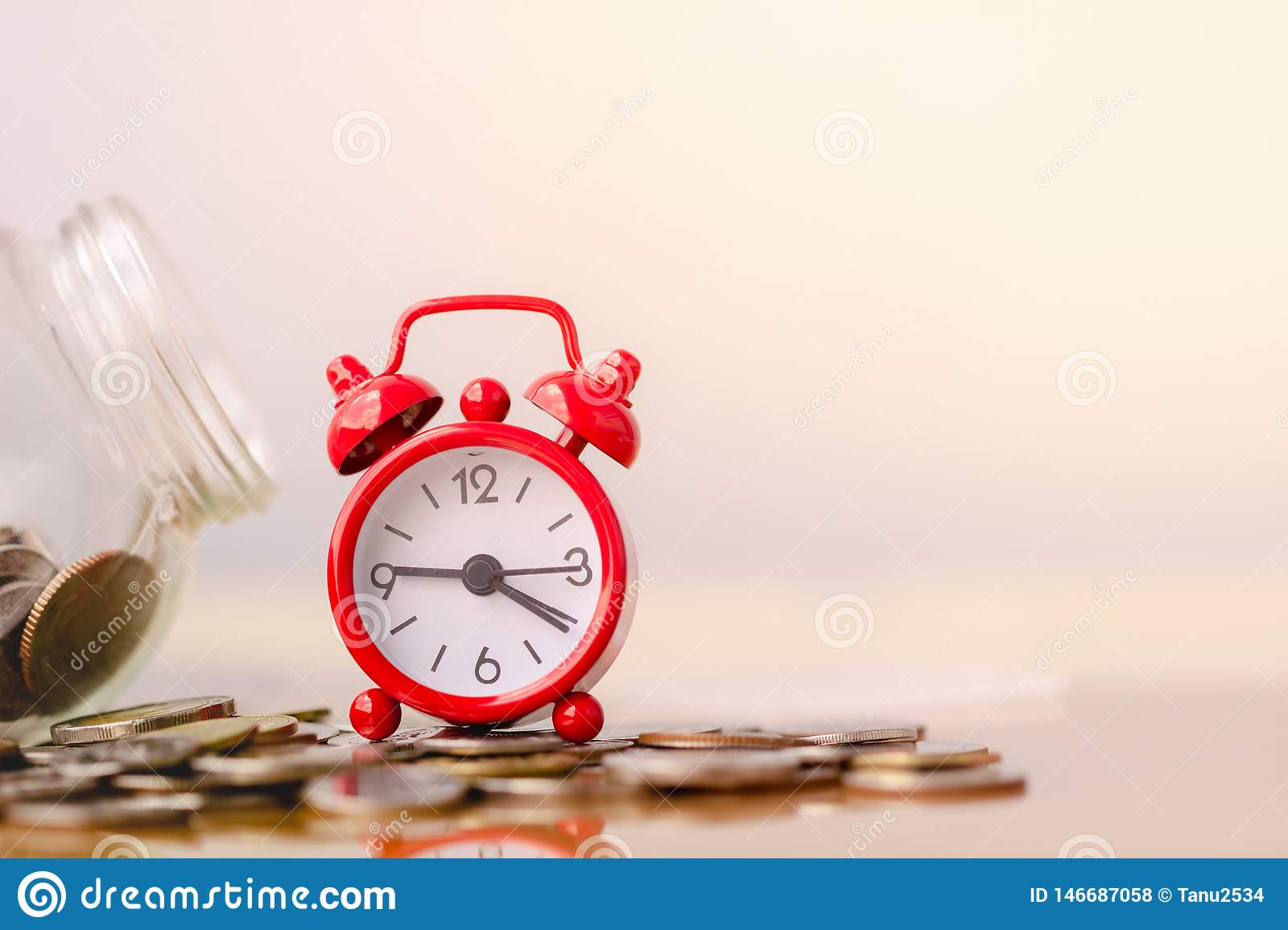 Red alarm clock on stack of coins in concept of savings and money growing or energy save. Business investment growth concept.
