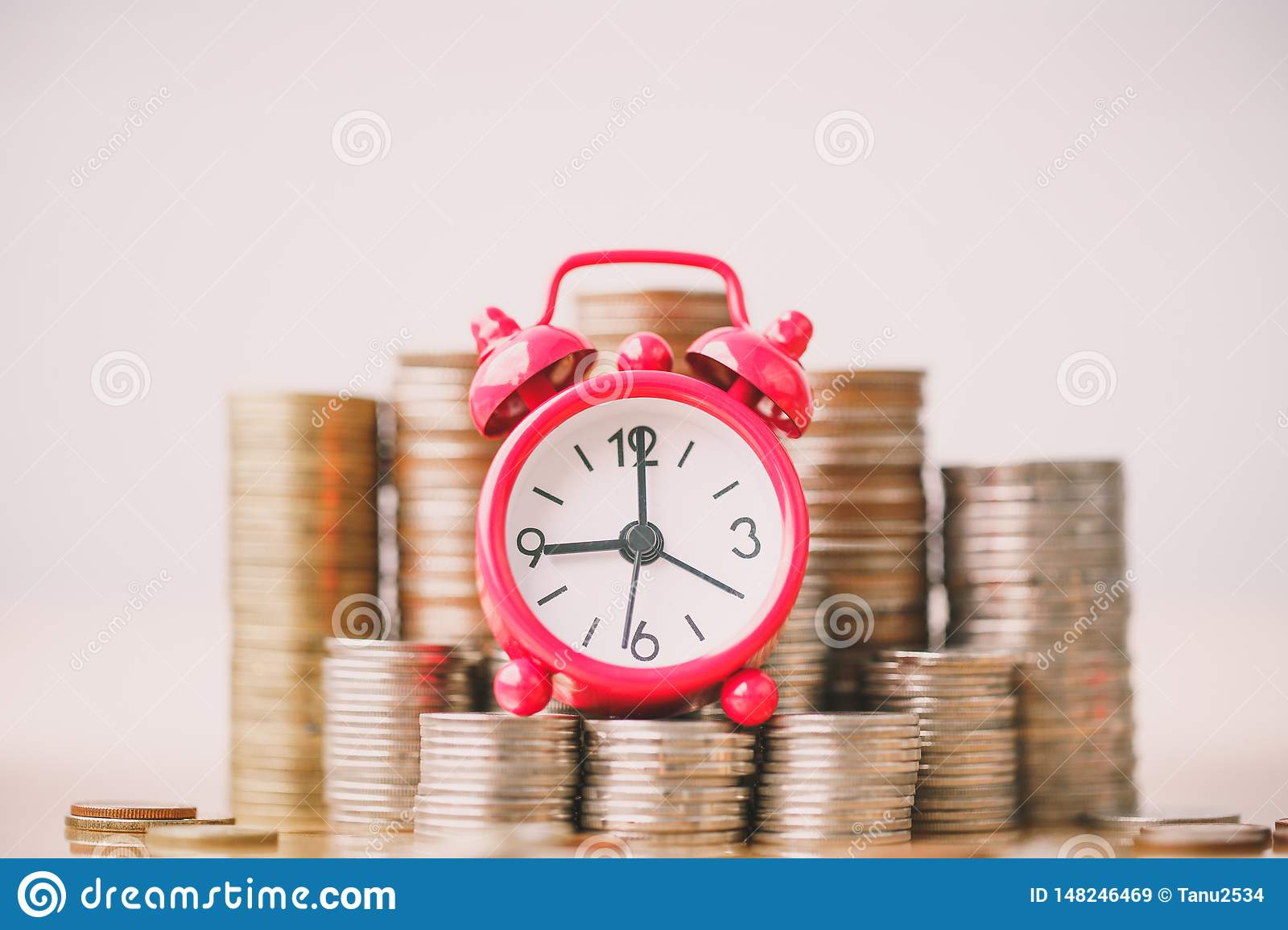 Red alarm clock on stack of coins in concept of savings and money growing or energy save.