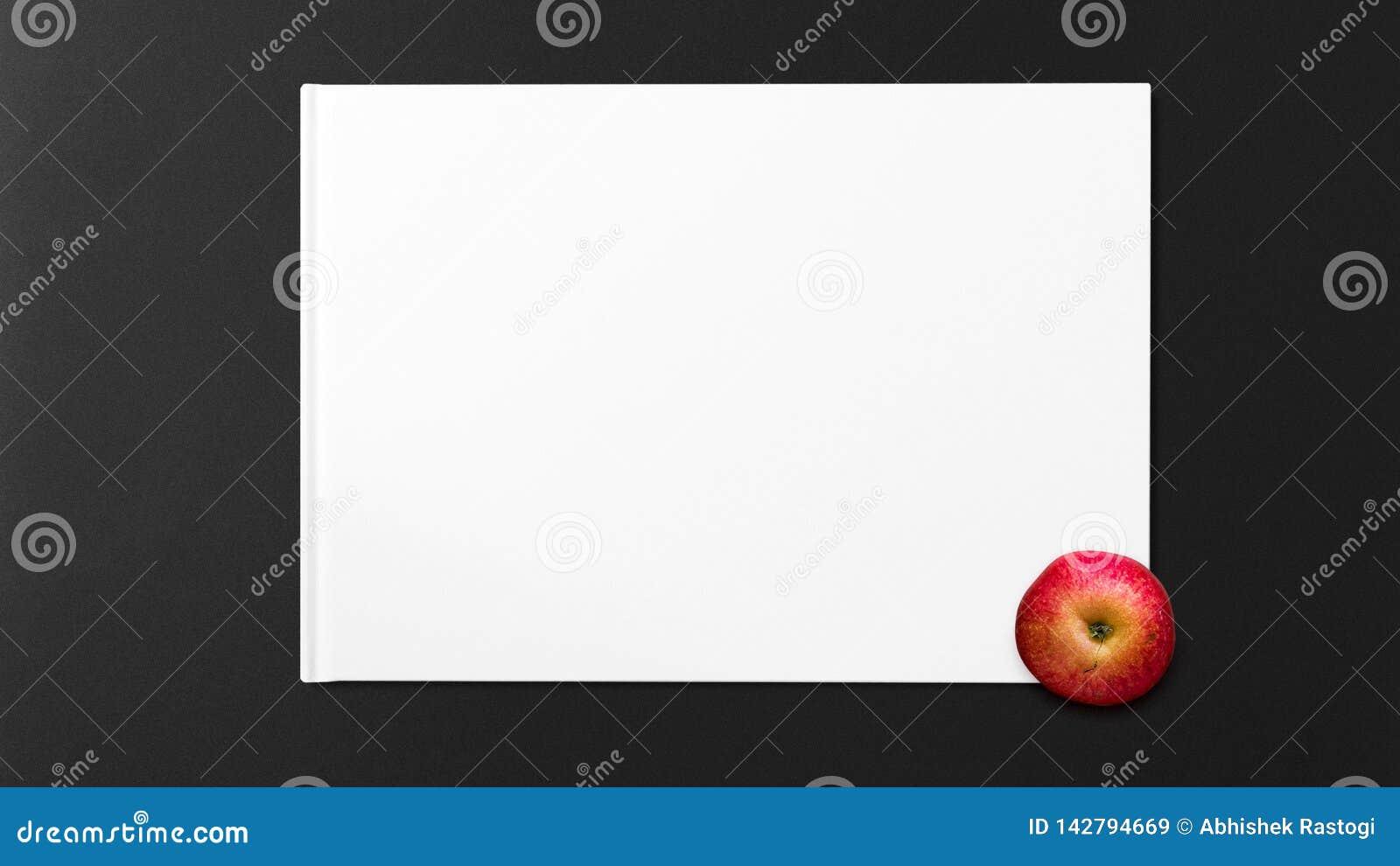 Red Apple on white paper on dark background