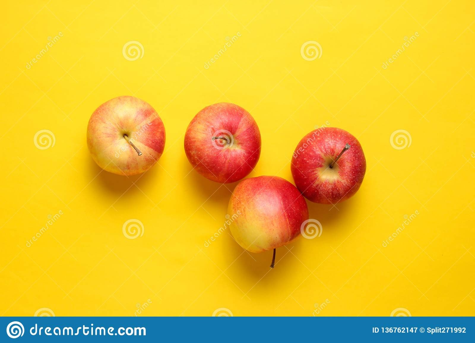 Red apples on yellow background