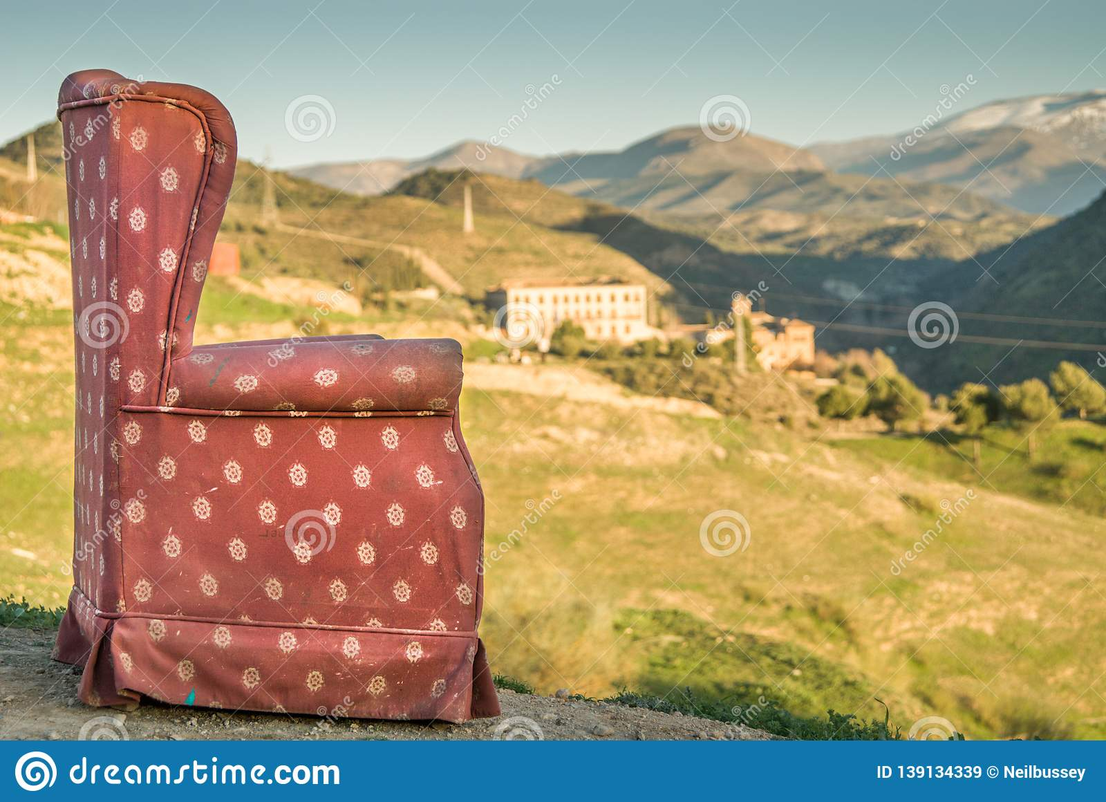 Red arm chair perched on hillside,Sacromonte caves,Granada,Andalucia,Spain