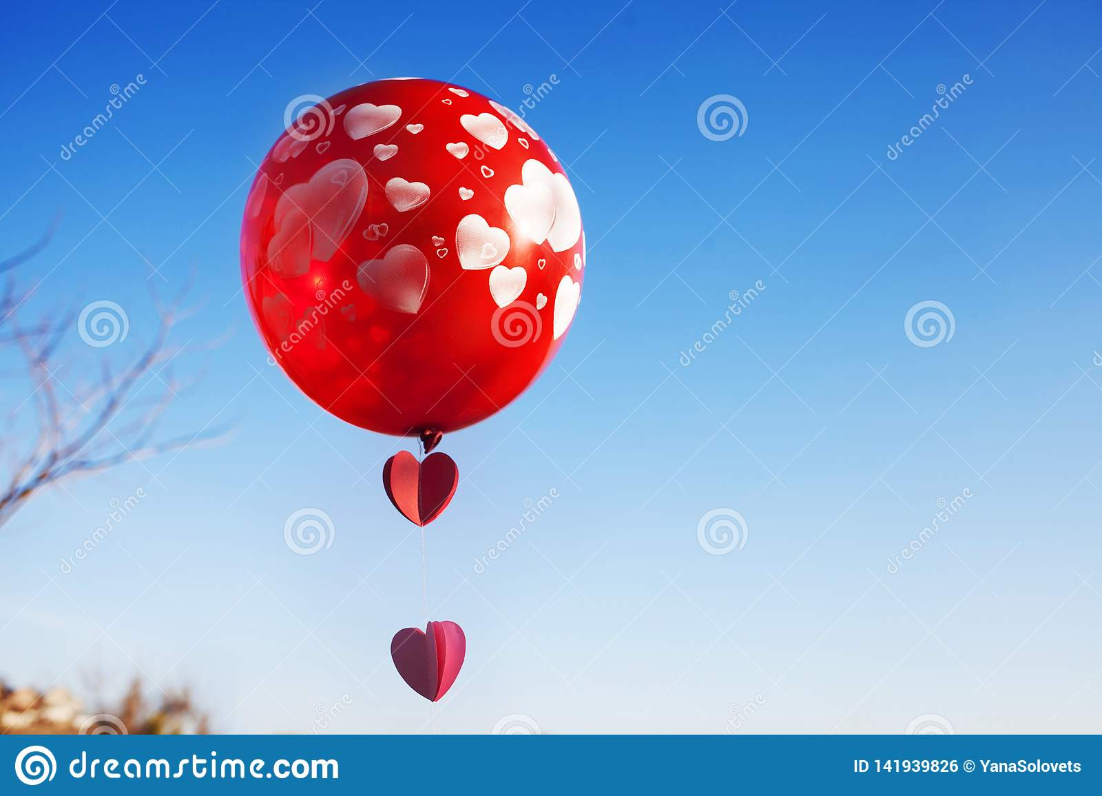 A little girl with red balloon on the blue sky.