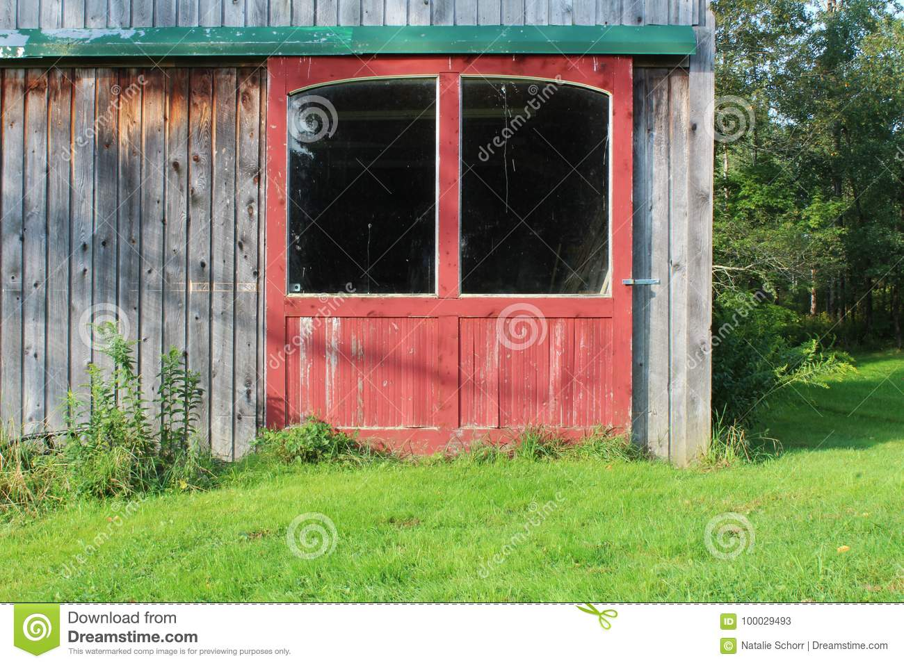 Red Barn Doors With Large Windows In Green Track On A Weathered Wood