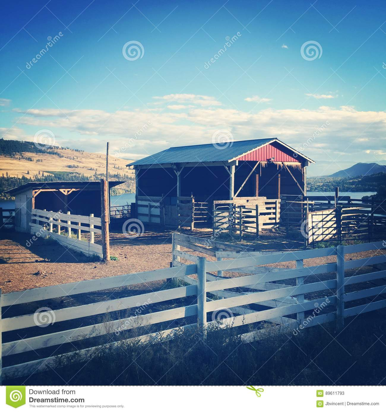 Red barn and white fence on hillside