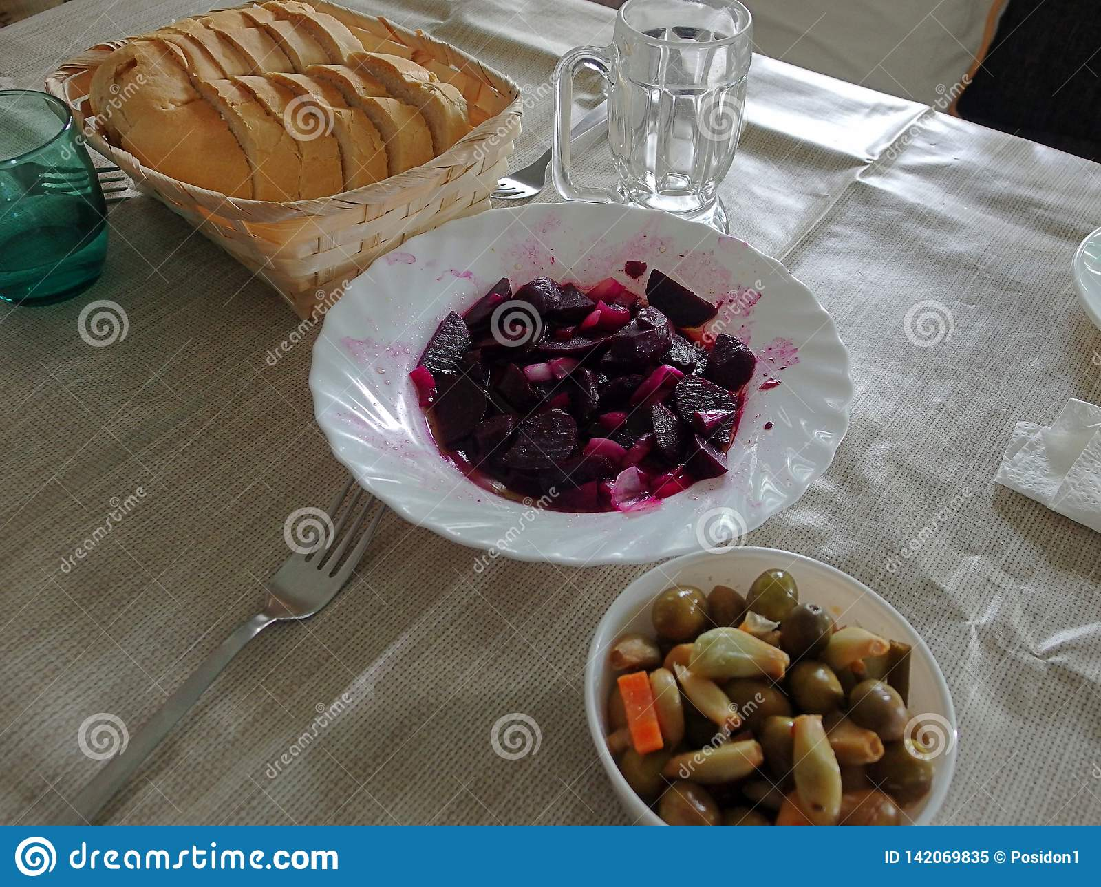 Red beet and olives with bread on a table