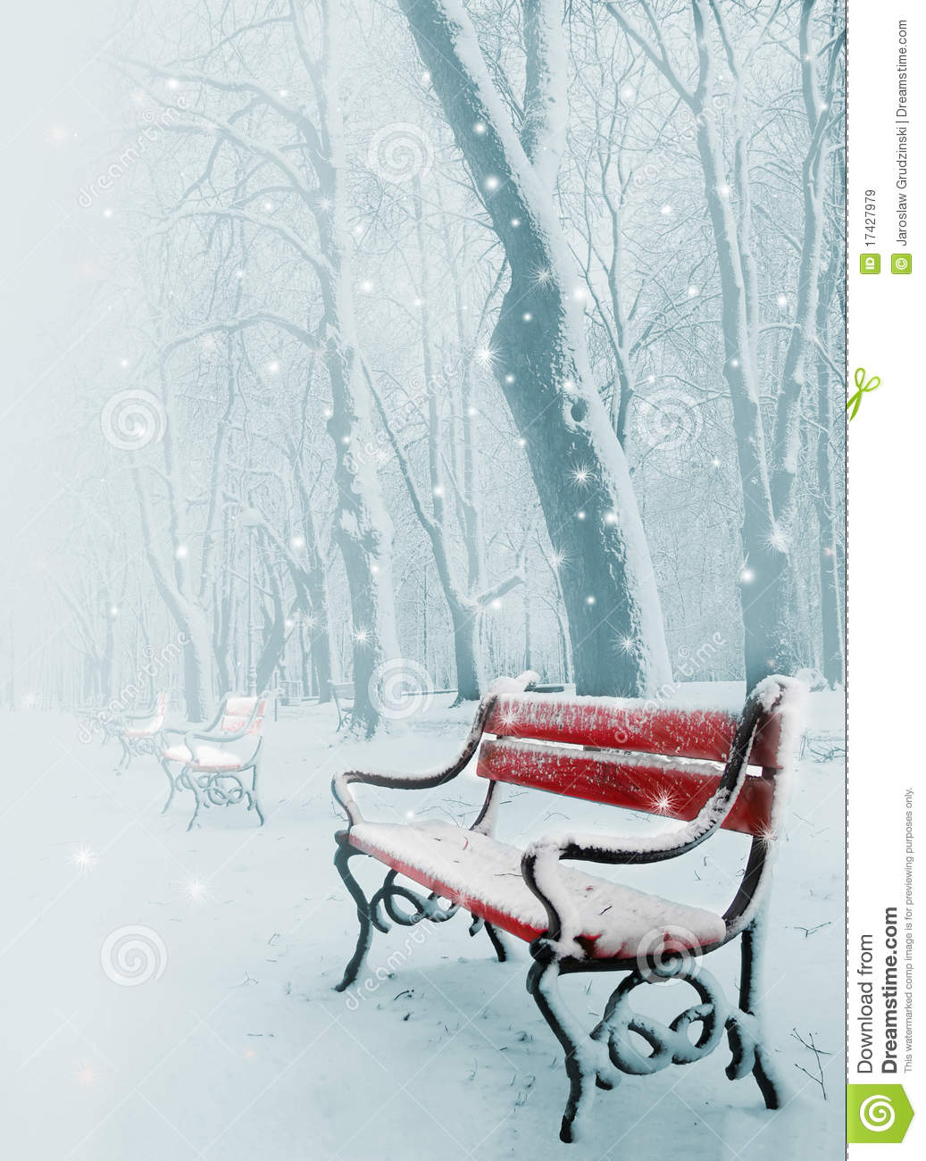 Row of red benches in the park in the snow in winter.