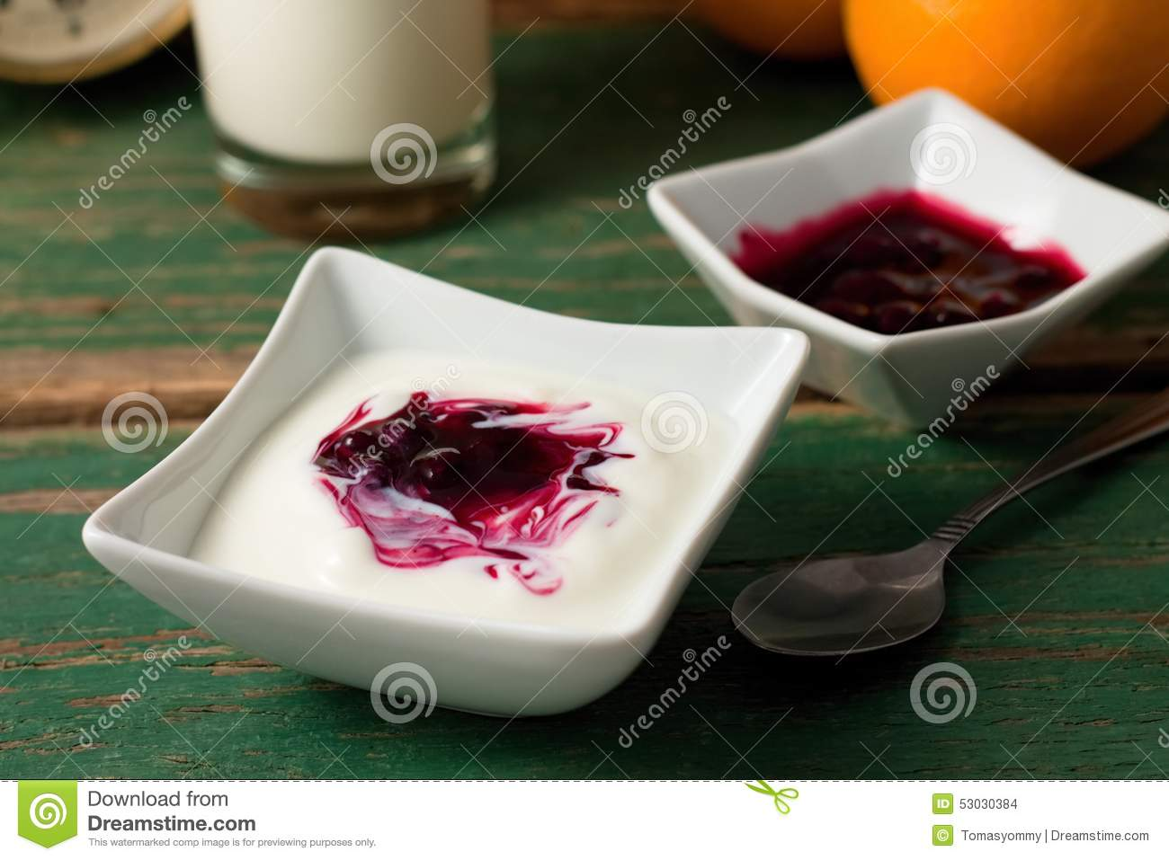 Red berry fruit in white yogurt placed with bowl on green table