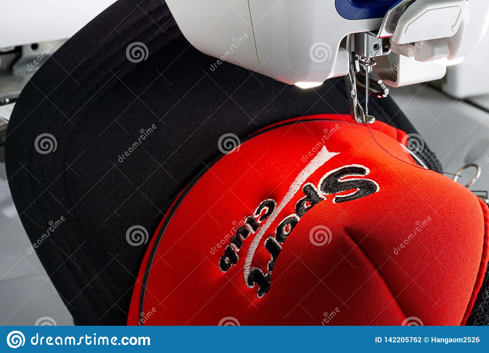 Red And Black Cap And Embroidery Machine Close Up Picture