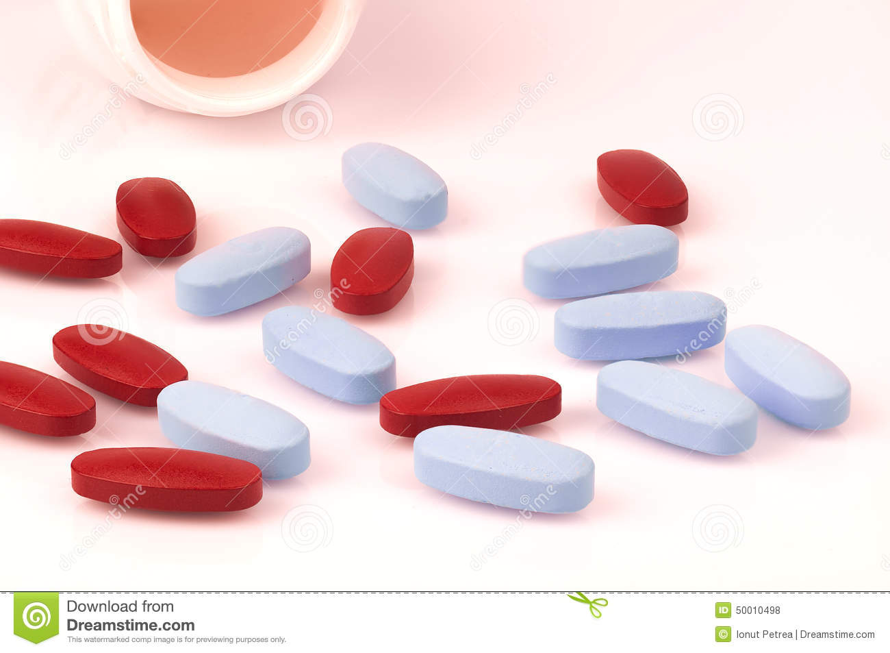white pills and bottle on blue background stock photo
