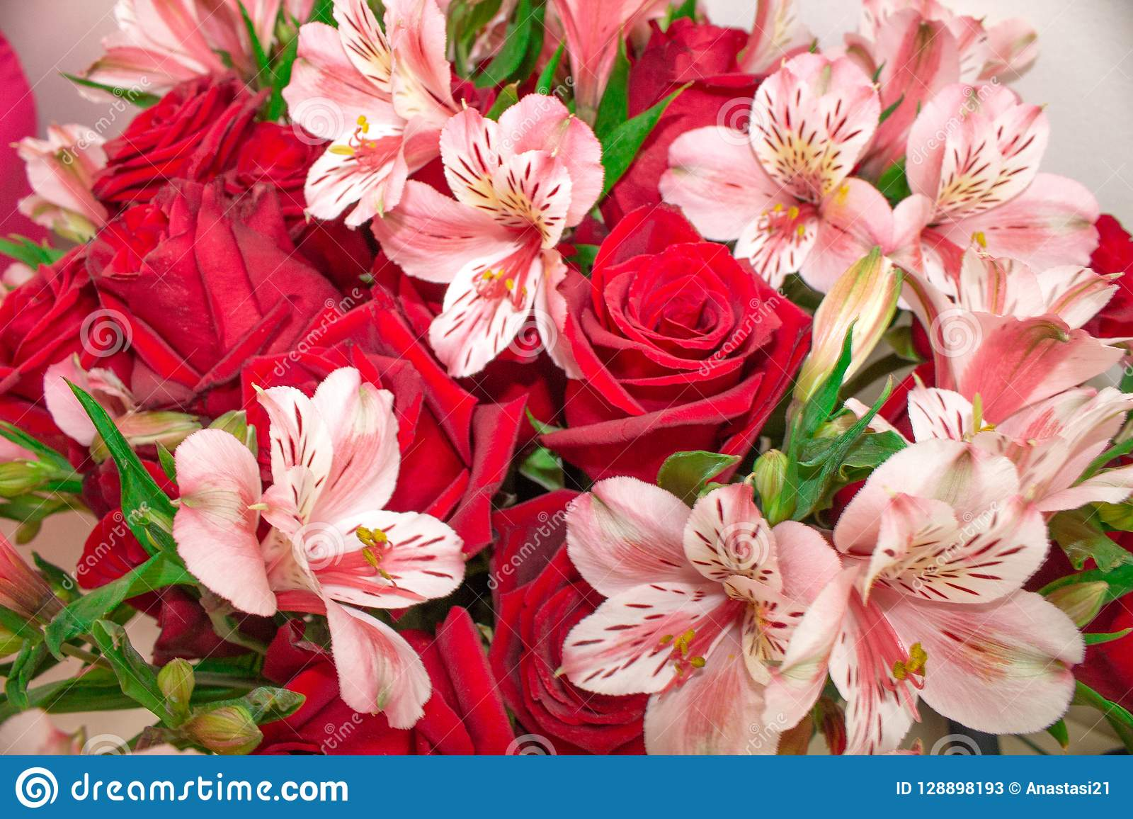 Red bouquet of flowers roses and Alstroemeria. Close-up.