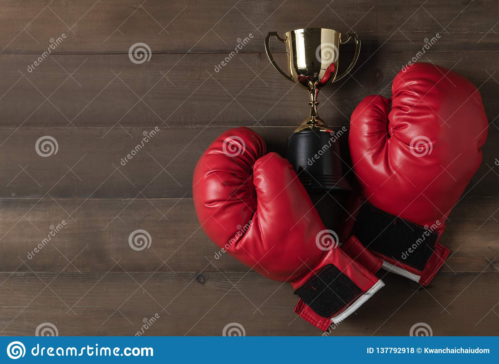 Red boxing glove and trophy on wood bcakground