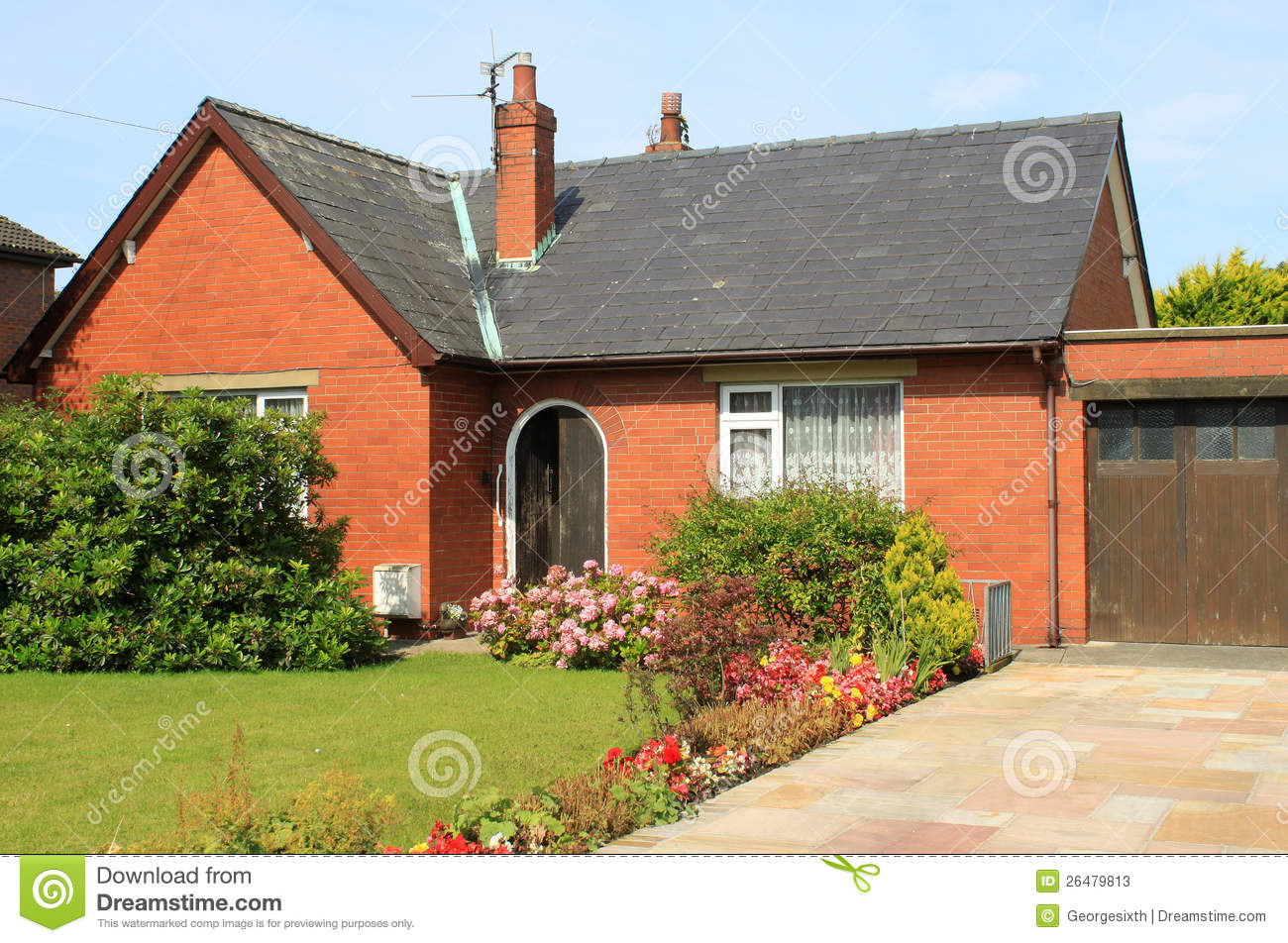 Red Brick Bungalow Flowers And Lawn In Garden