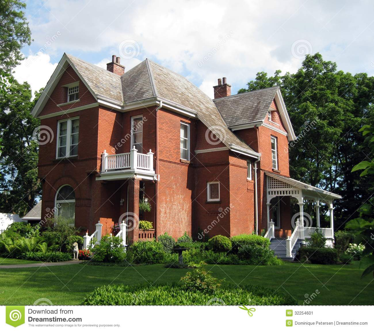 A Beautiful Old Red Brick Century Home With Side Porch And Second Story Balcony And Lush Landscaping
