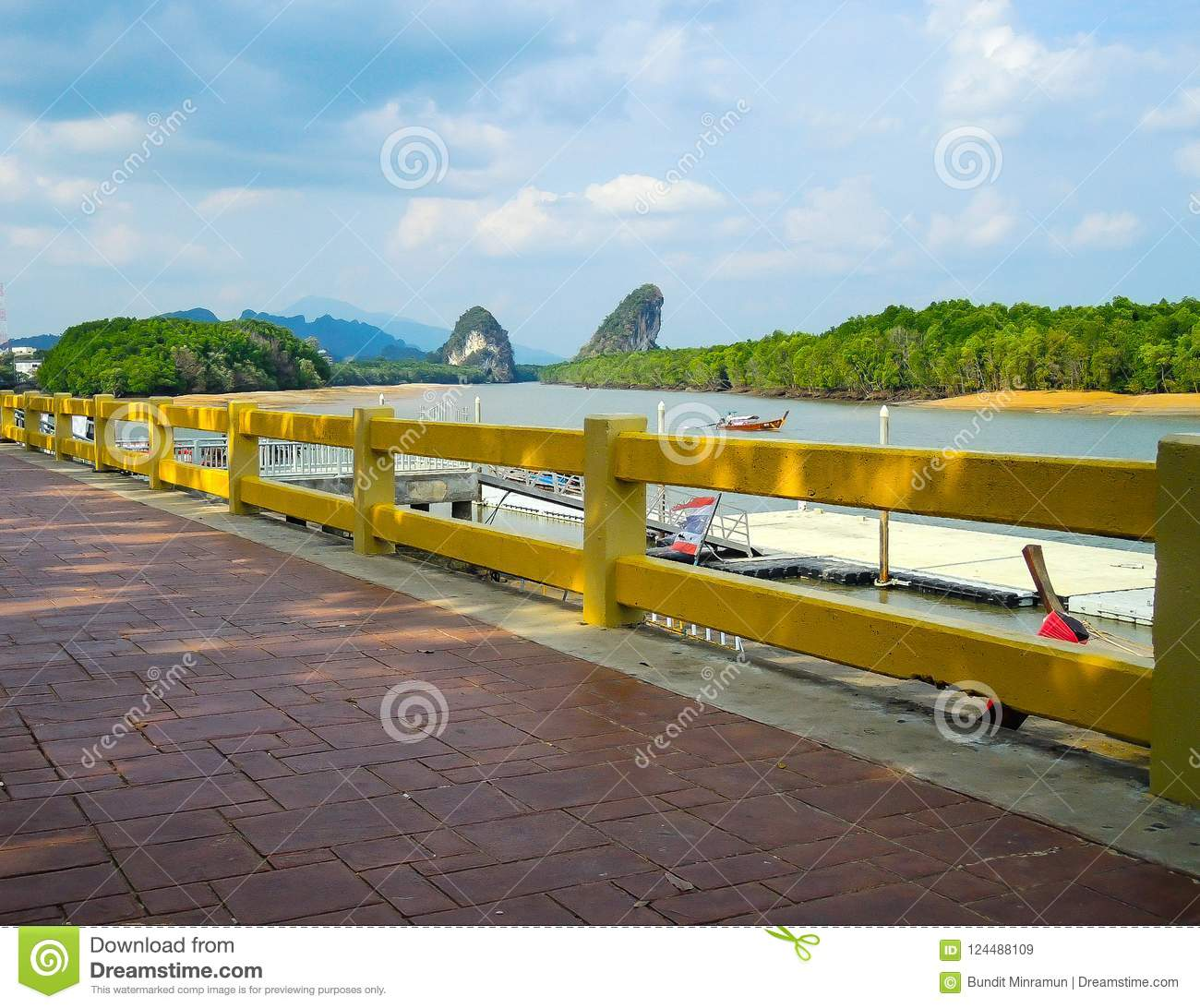 Red brick path way with scenic waterfront mountain view in Krabi, Thailand.