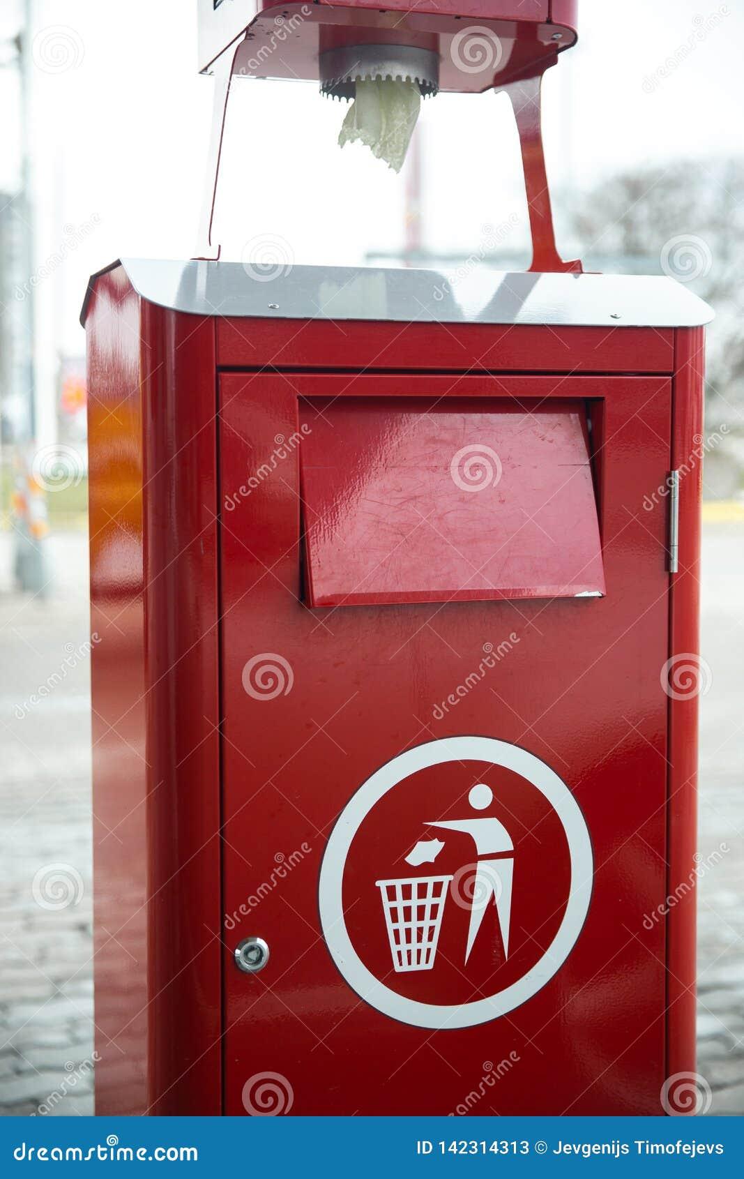 Red bright metal trash bin at a gas station