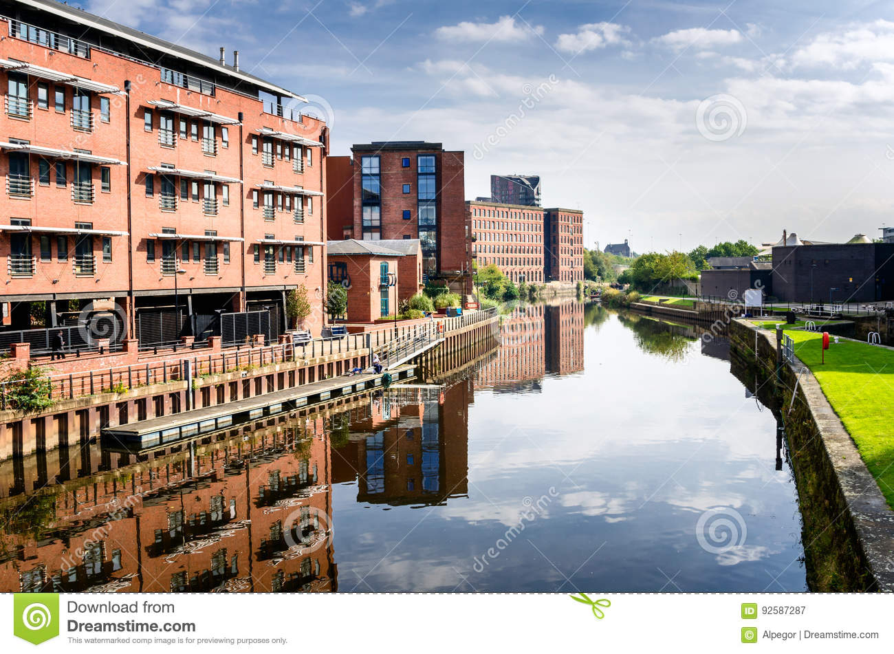 Red Brik Buildings alongside a River and Blue Sky with Clouds