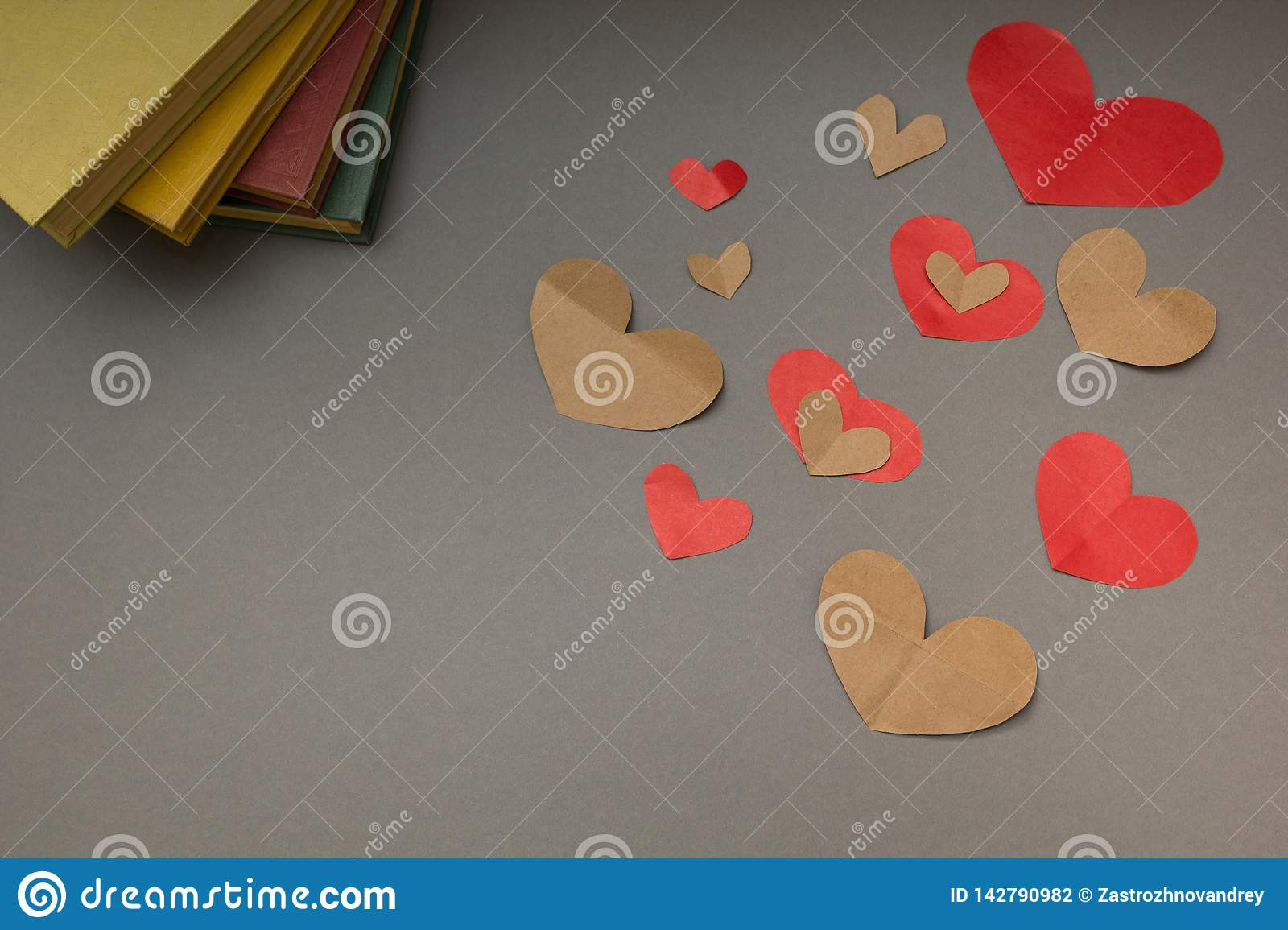Red and brown hearts and the book on a gray background