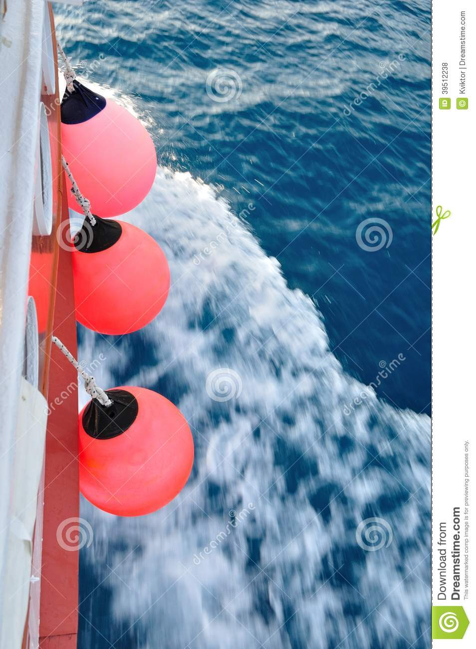 Red buoy on body of moving ship
