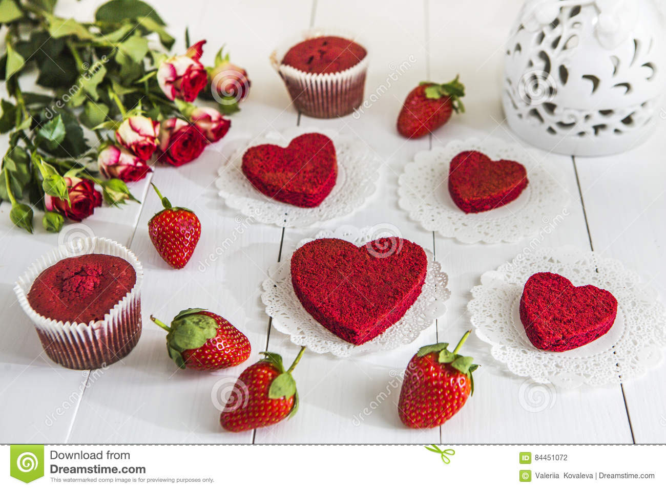 Red cake without cream `red velvet` on a white wooden table, decorated with strawberries, roses and white openwork vase with a hea