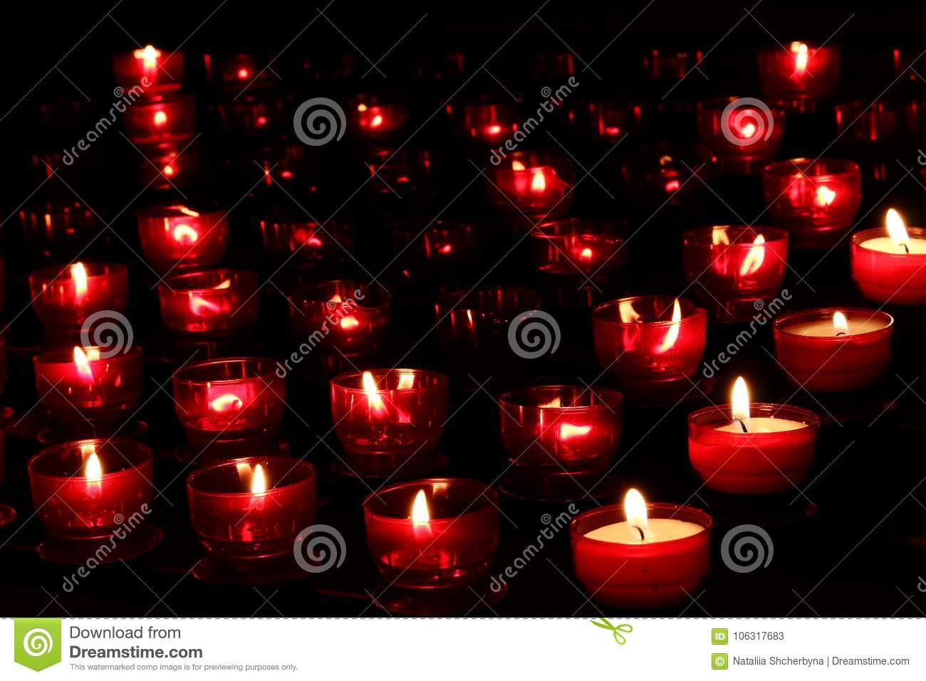 Red candles with glowing lights in darkness in church. Peace and hope background. Religion concept.