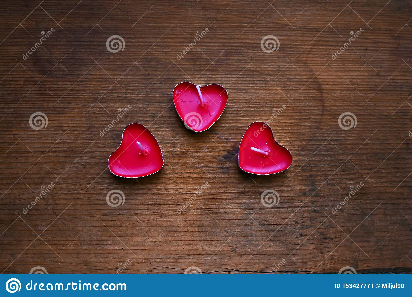 Red candles on wooden background
