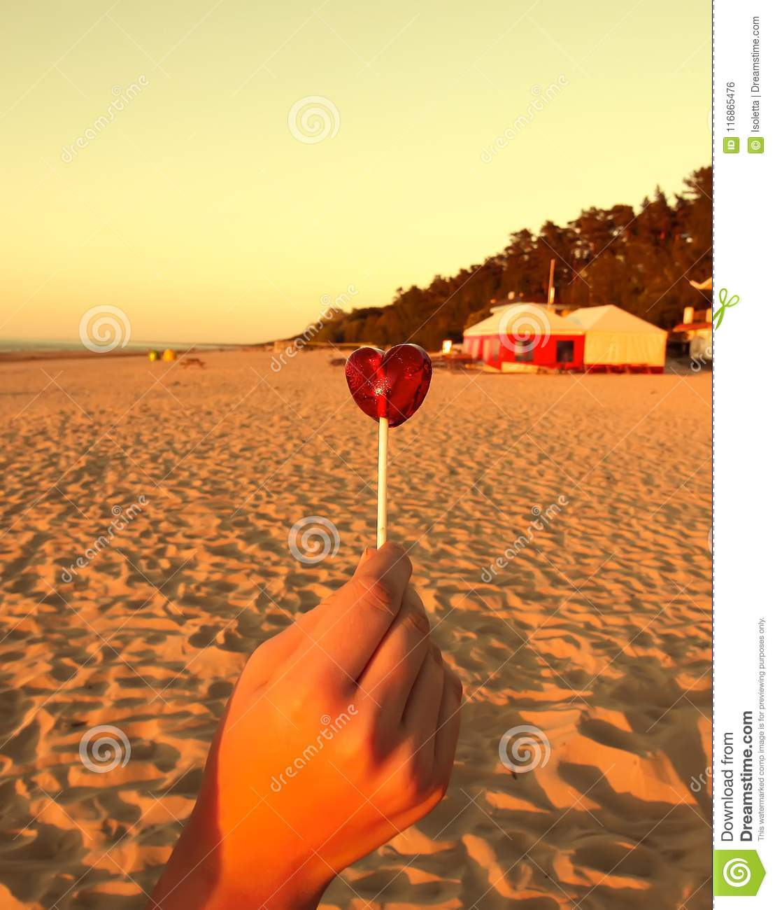 Red candy in shape of a heart in a hand on sandy beach background. Sunset warm light. Vertical shot.